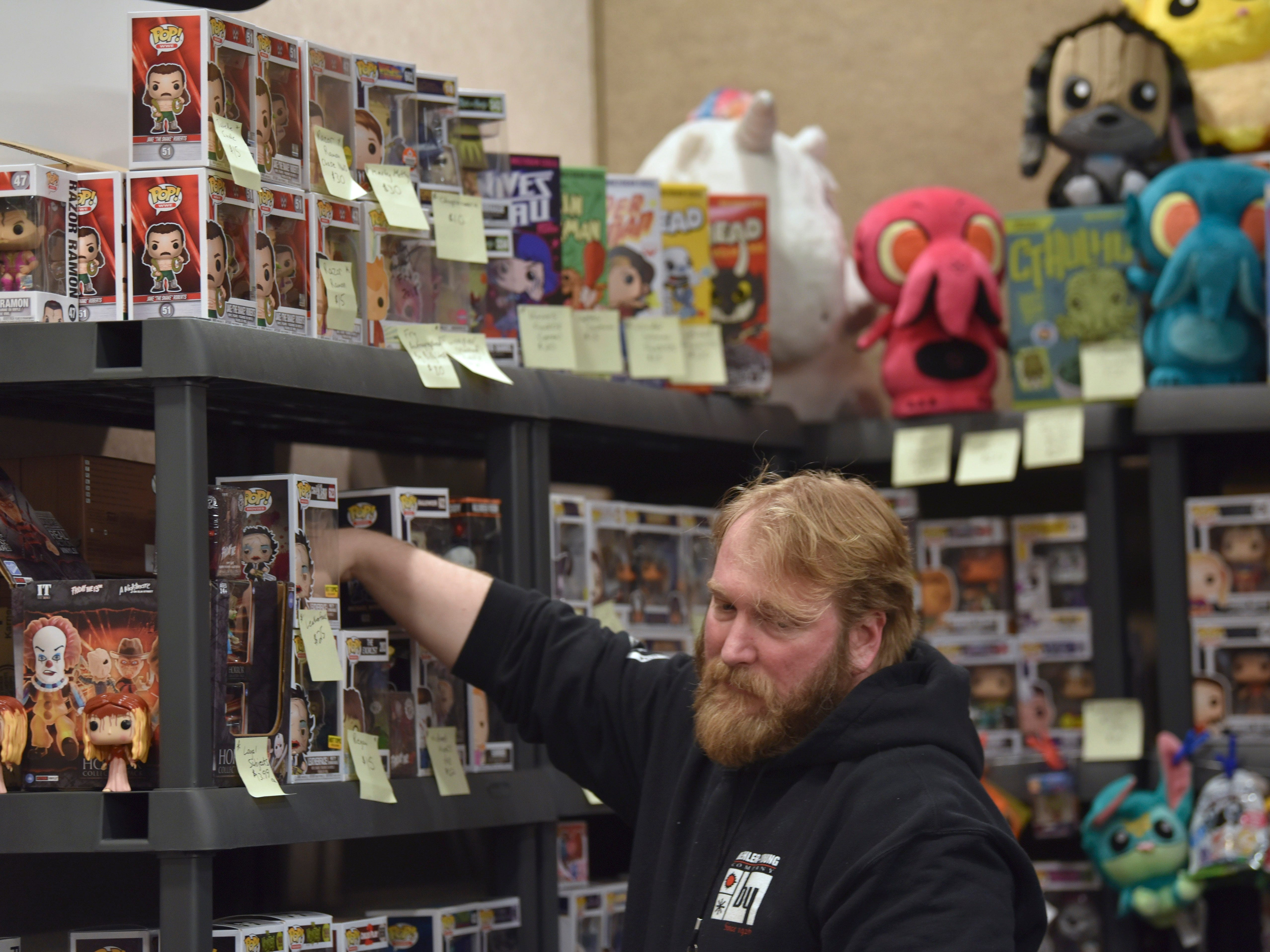 Throne of Toys employee Dane Wright, 42, of Westland, straightens out merchandise in the vendors area.