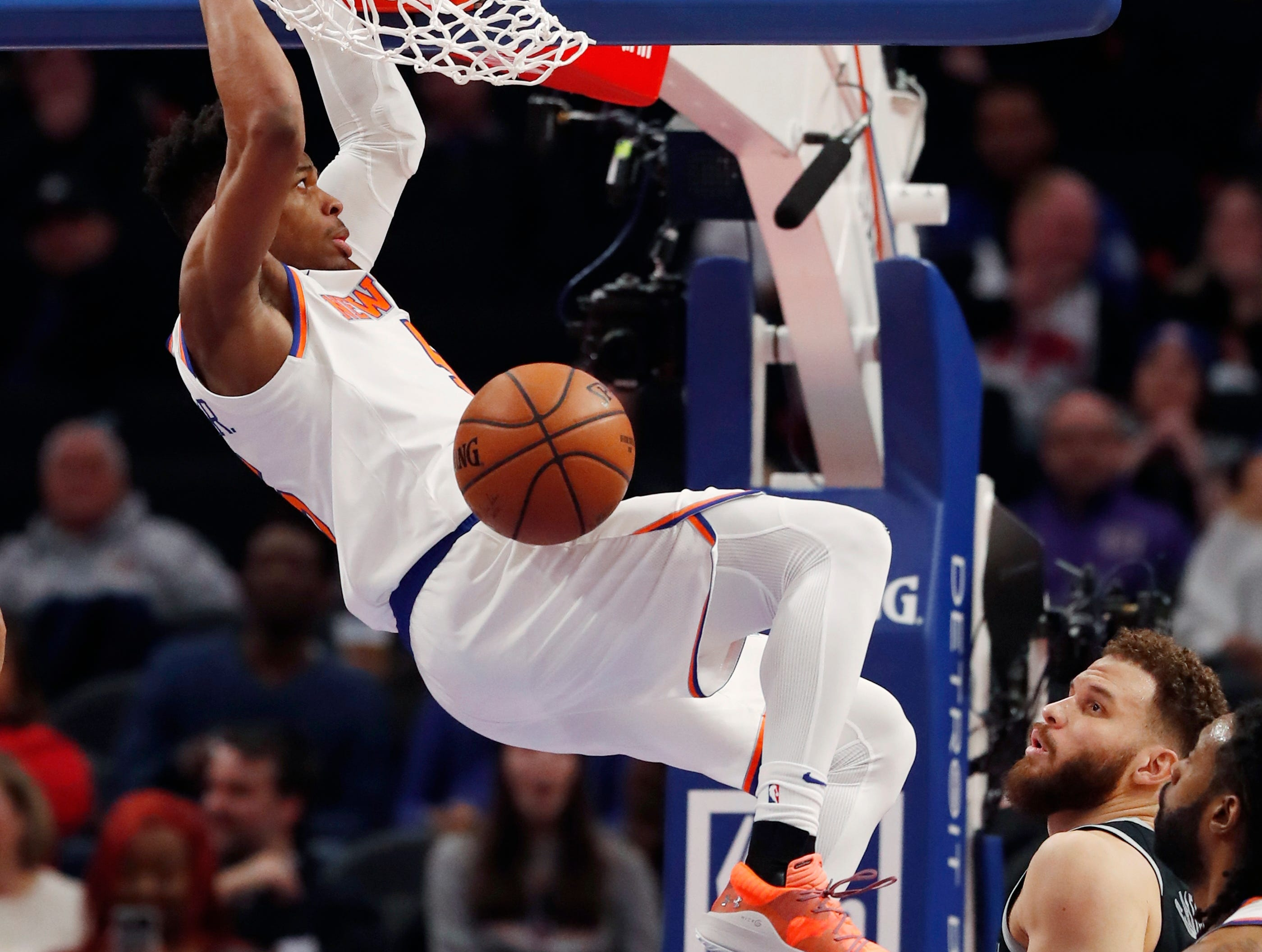New York Knicks guard Dennis Smith Jr. dunks as Detroit Pistons forward Blake Griffin watches during the first half of an NBA basketball game Friday, Feb. 8, 2019, in Detroit.