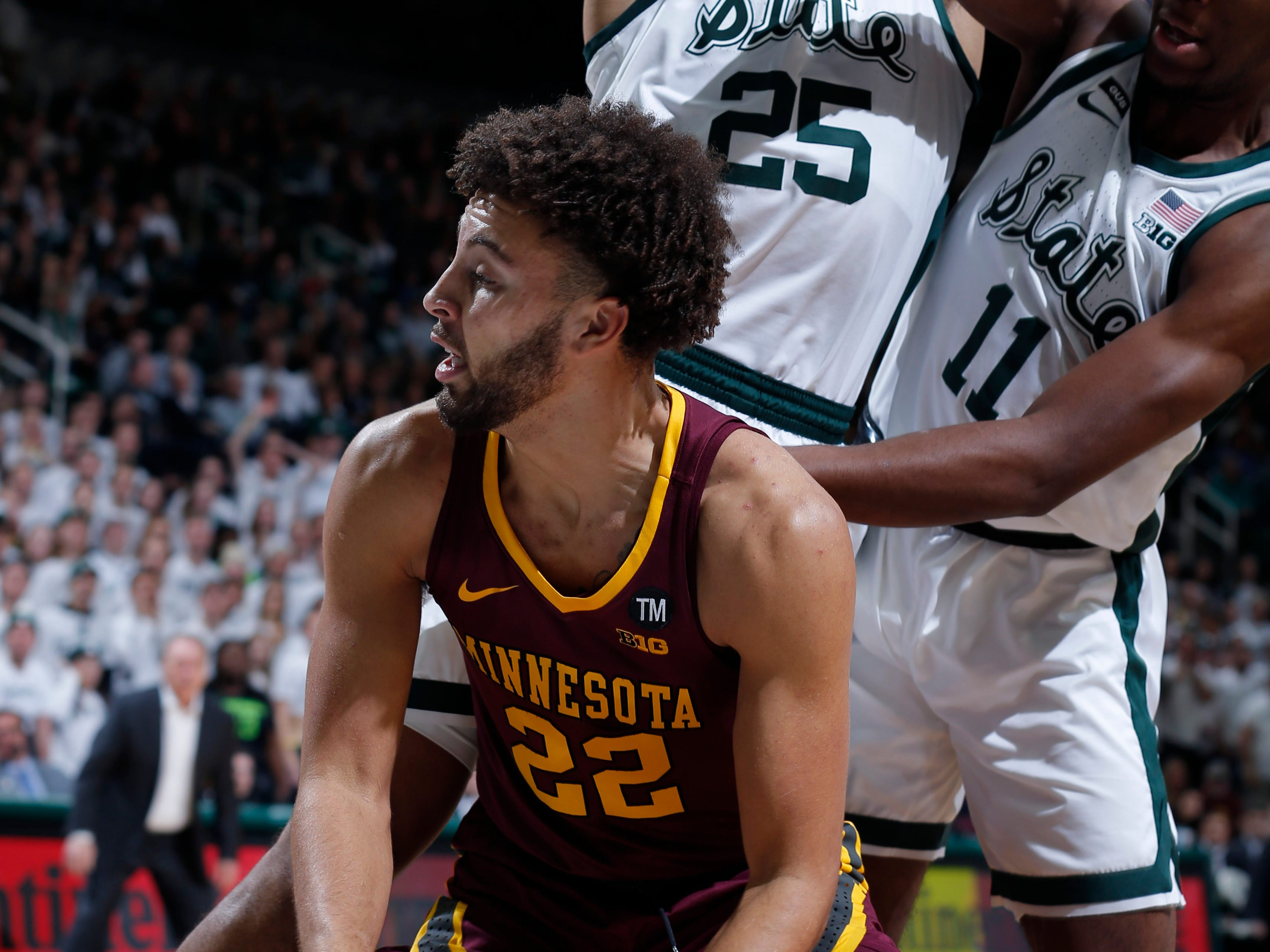 Minnesota's Gabe Kalscheur (22) is pressured by Michigan State's Kenny Goins (25) and Aaron Henry (11) during the first half.