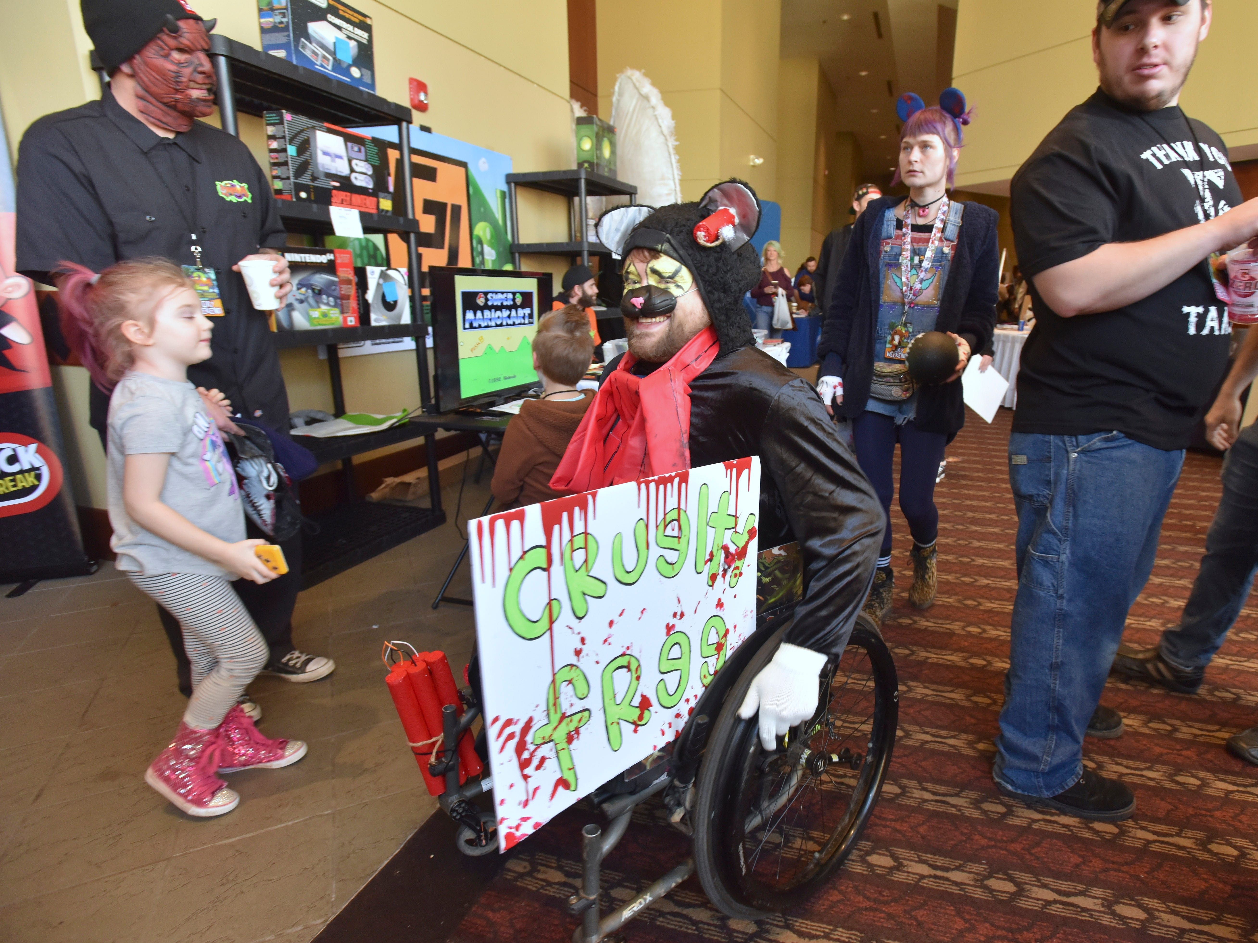 Christopher Allen McCoy, 34, of Indianapolis, portrays 'Scratchy,' from 'Ichy and Scratchy,' as he arrives at the convention. McCoy is in a wheelchair after losing both legs and his right hand when a moped he was riding exploded nine years ago.