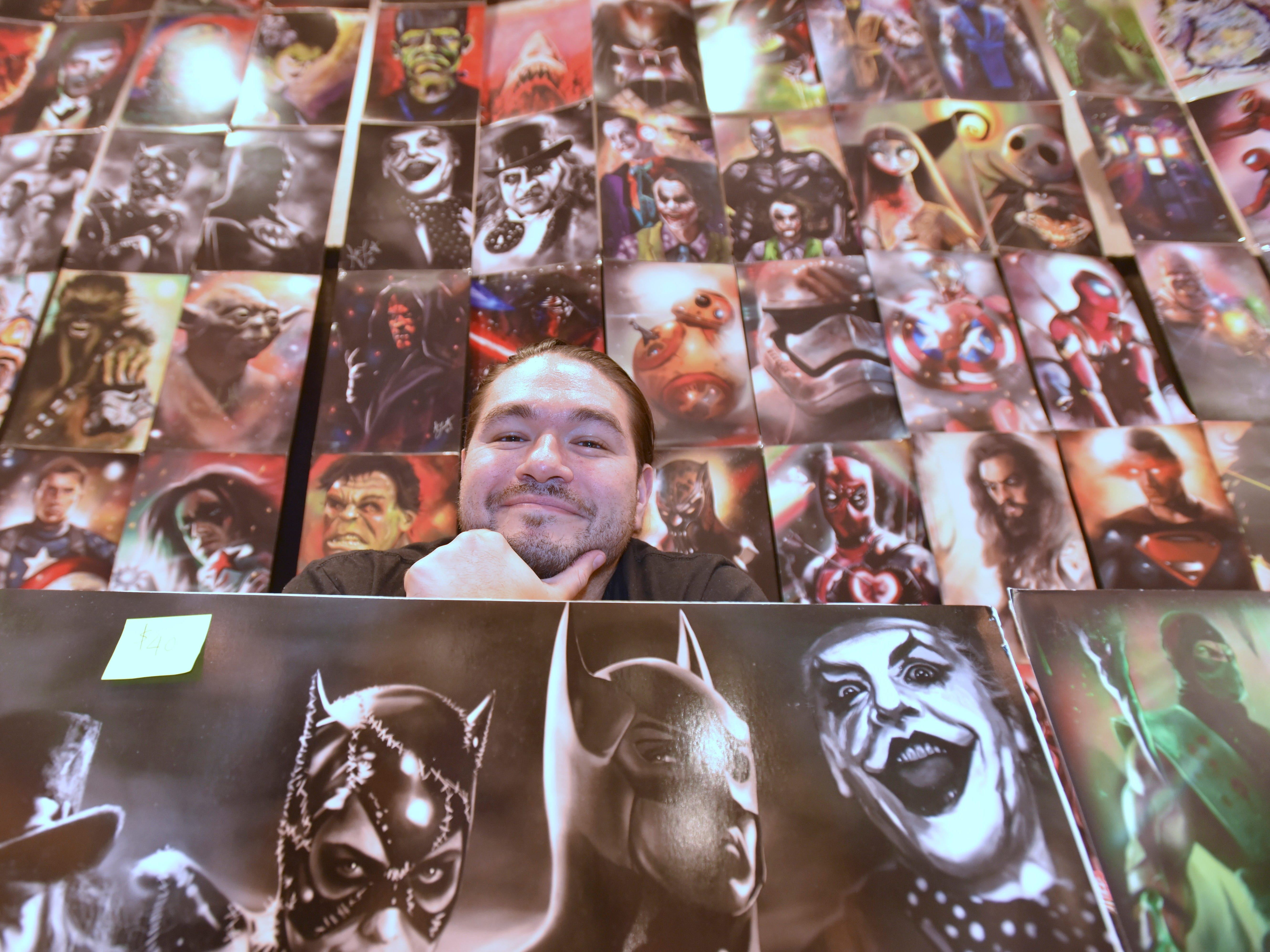 Comic book cover artist Aaron Lambert, 35, of Cincinnati, Ohio, poses with more than 100 paintings for sale at his booth, Saturday. He has created at least 10 comic book covers.