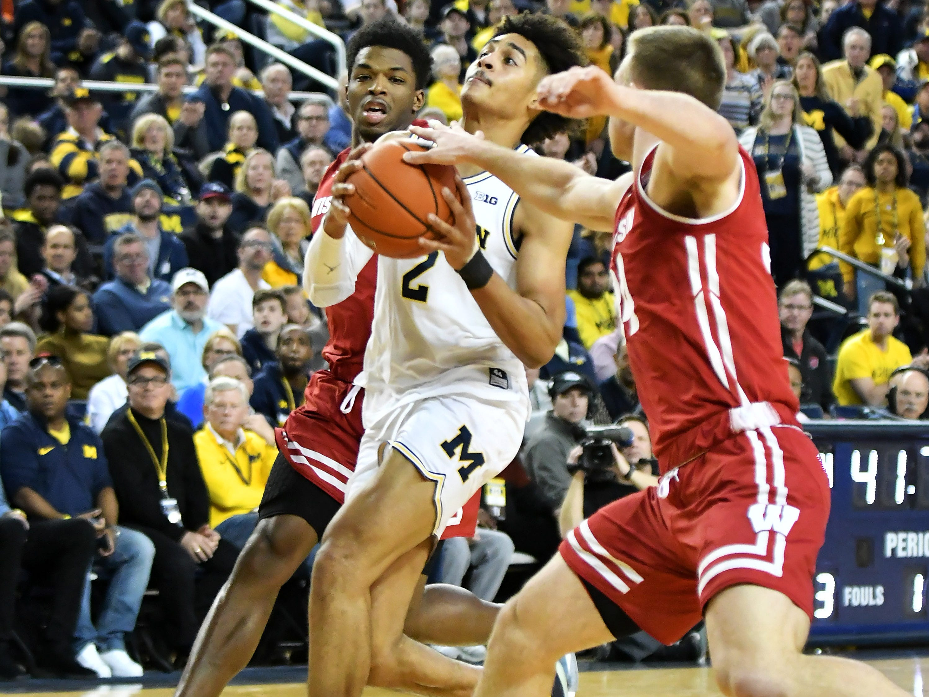 Wisconsin guard Khalil Iverson (21) and Wisconsin guard Brad Davison (34) defend a drive by Michigan guard Jordan Poole (2) in the first half.
