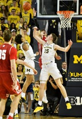 Michigan center Jon Teske (15) and Michigan guard Jordan Poole (2) battle Wisconsin forward Ethan Happ (22) for the ball in the second half.