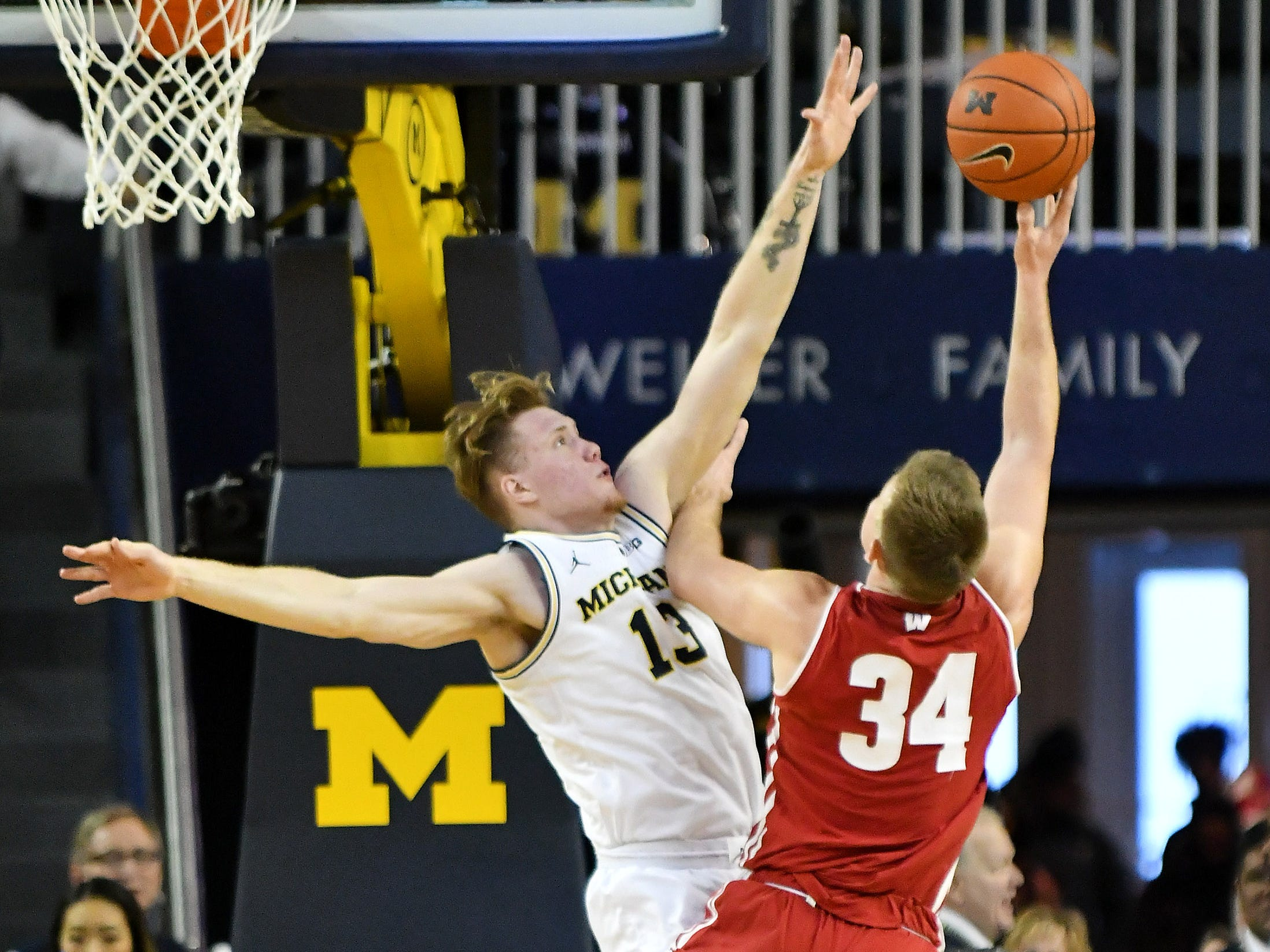 Michigan forward Ignas Brazdeikis (13) defends a shot by Wisconsin guard Brad Davison (34) in the second half.