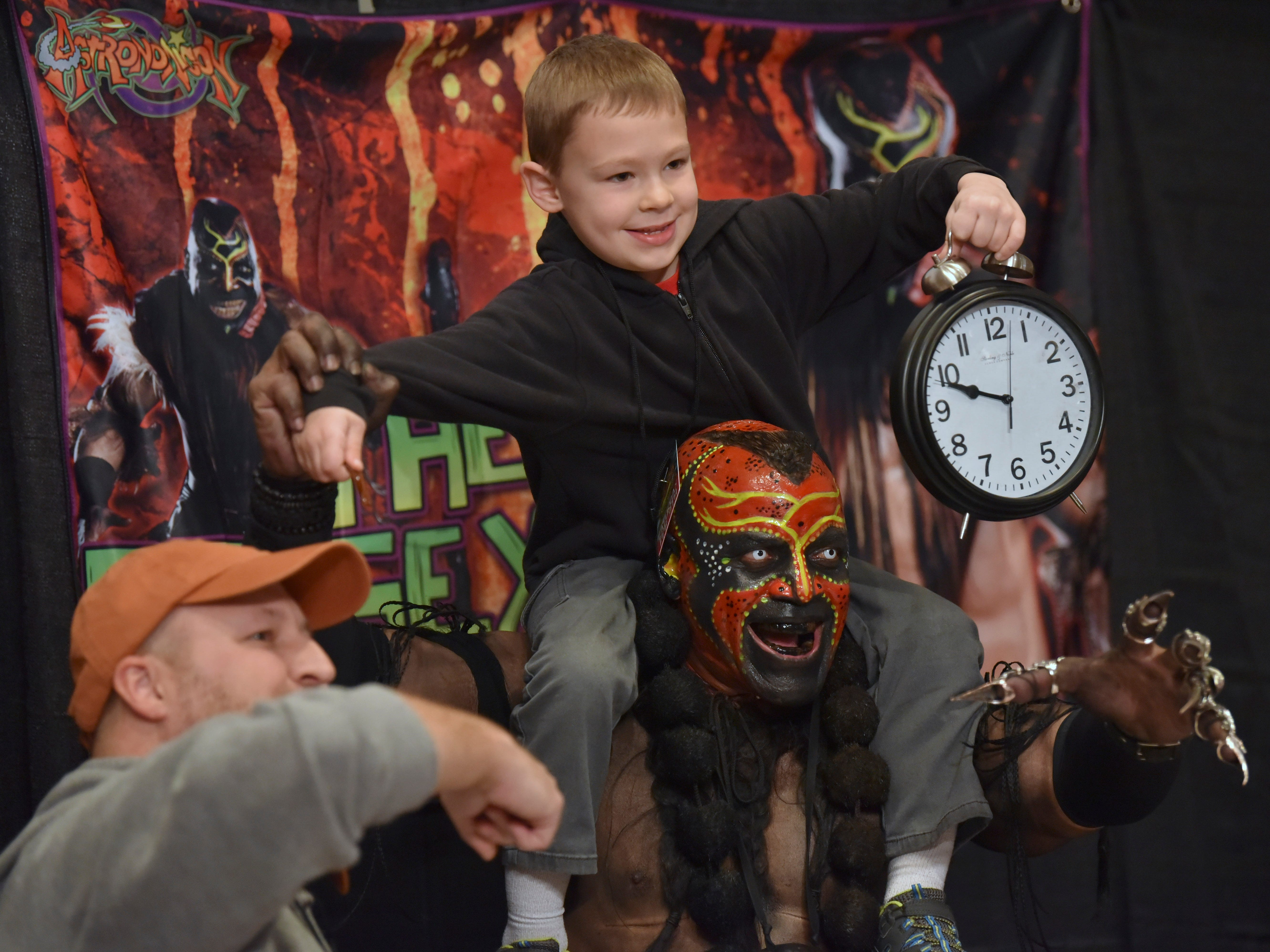 Kyle Anderson, left, 42, and his son, Noah, 6, both of Grand Rapids, pose with WWE Superstar wrestler 'The Boogeyman,' portrayed by Marty Wright, of Denver, Colorado.