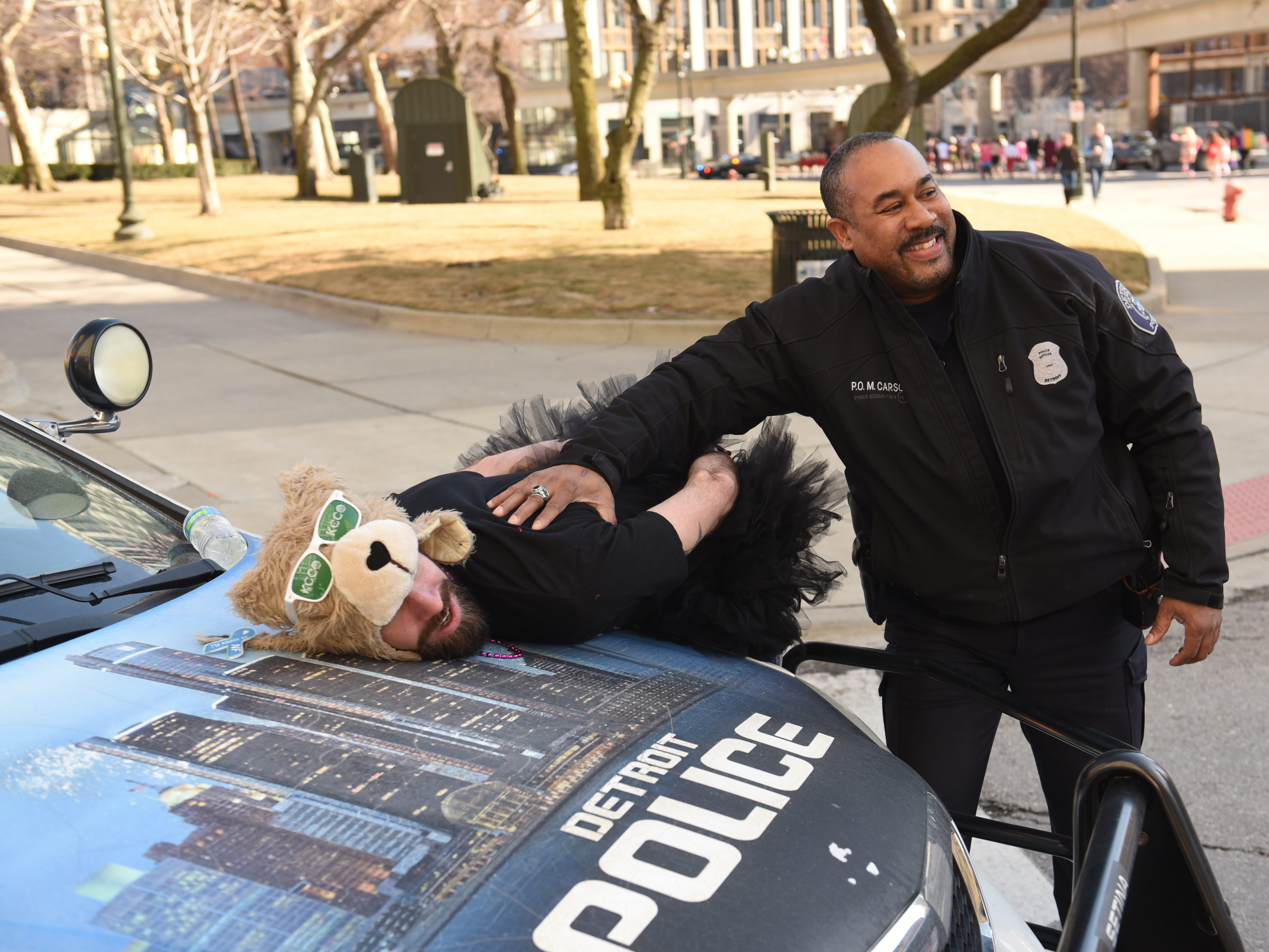 Benjamin Fisher of Caseville has fun with a Detroit Police officer at Grand Circus Park for Cupid's Undie Run .