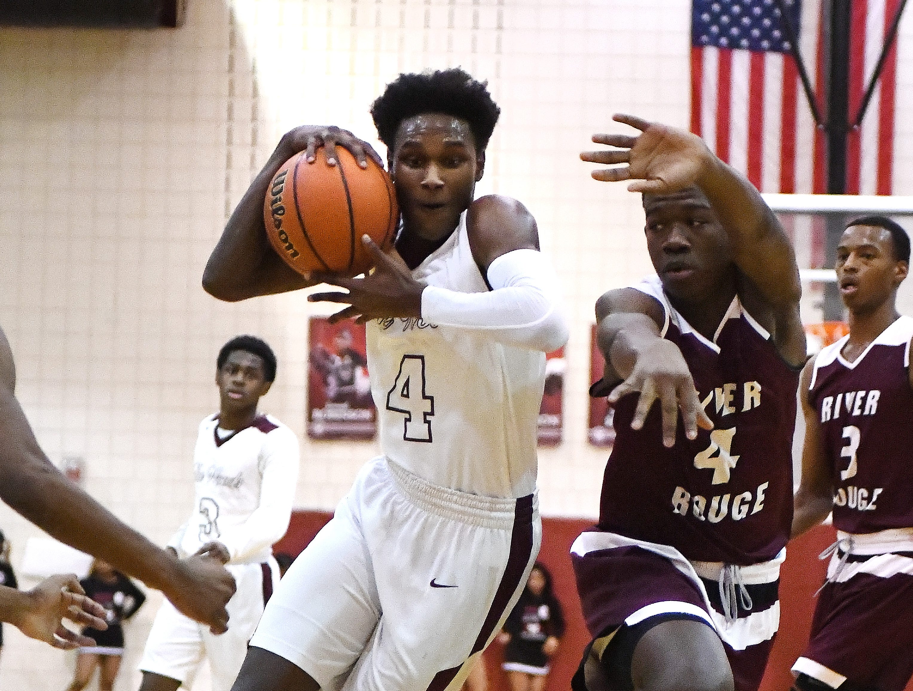 Harper Wood's Daniel Briggs drives on River Rouge's Legend Geeter in the first half. River Rouge High School at Harper Woods boys basketball in Harper Woods, Michigan on February 8, 2019.