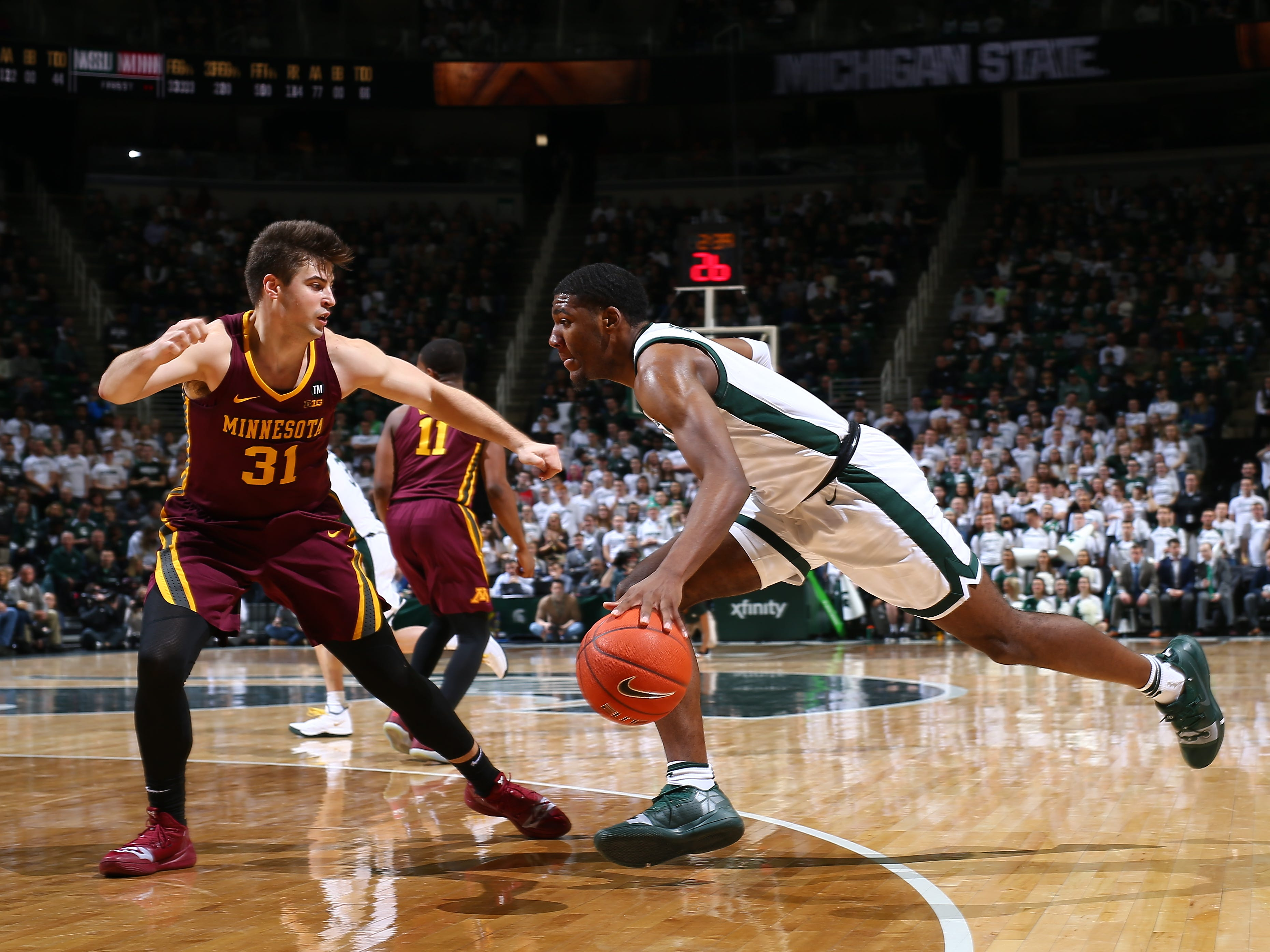 AAron Henry of the Michigan State Spartans drives to the basket while defended by Brock Stull in the first half.