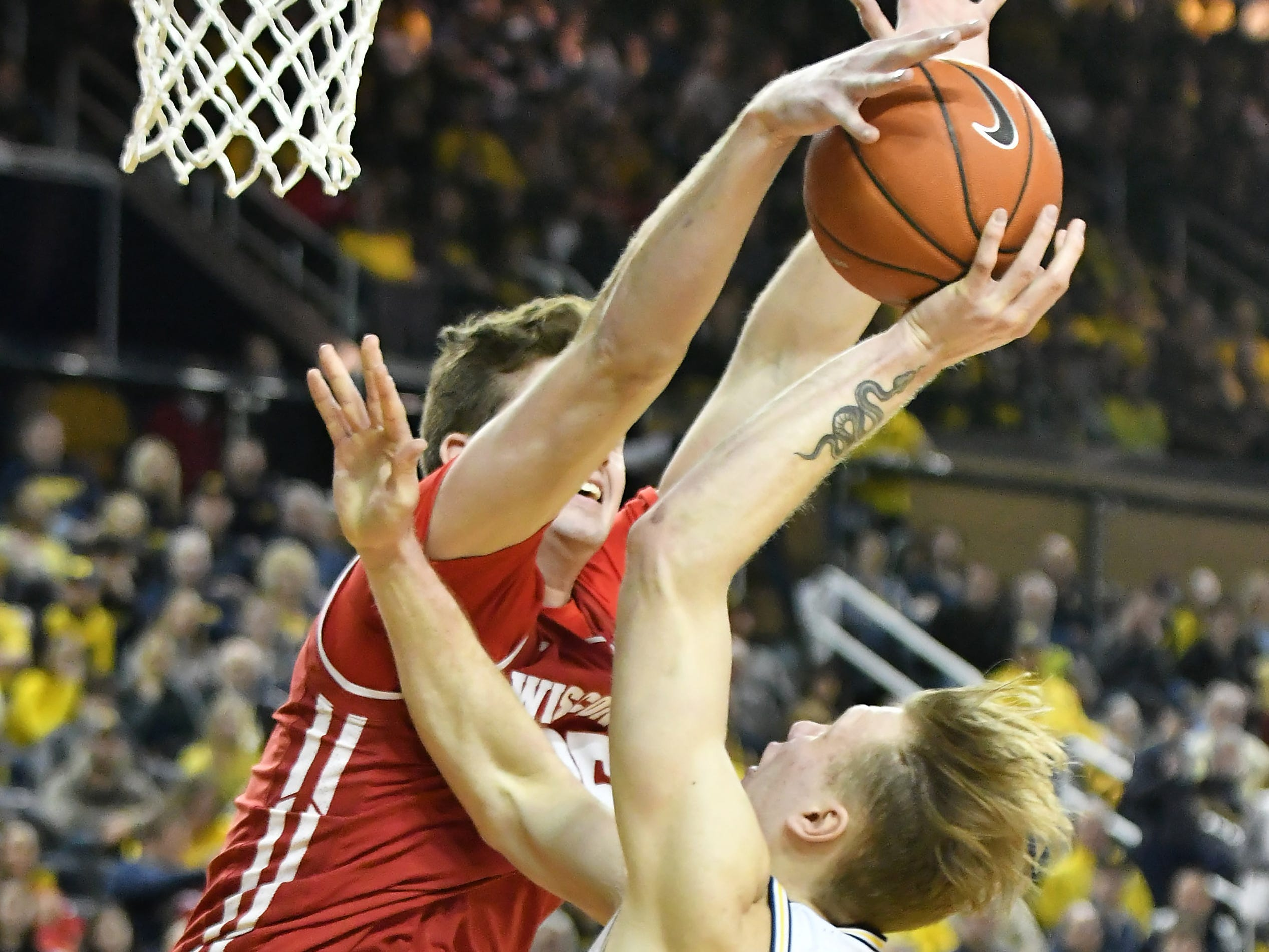 Wisconsin forward Nate Reuvers (35) blocks a shot attempt by Michigan forward Ignas Brazdeikis (13) in the first half.