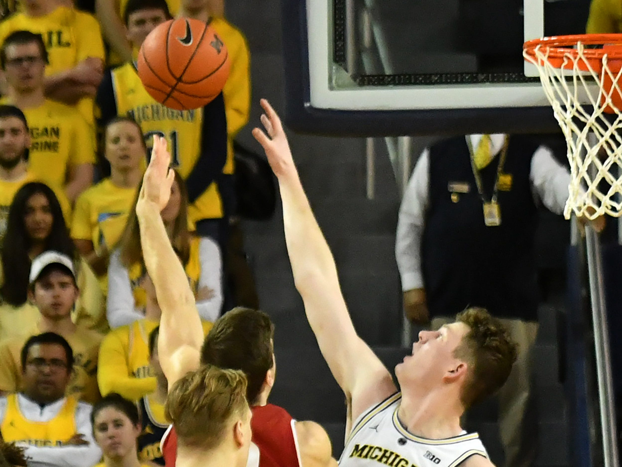 Michigan center Jon Teske (15) defends a shot by Wisconsin forward Ethan Happ (22) in the second half.