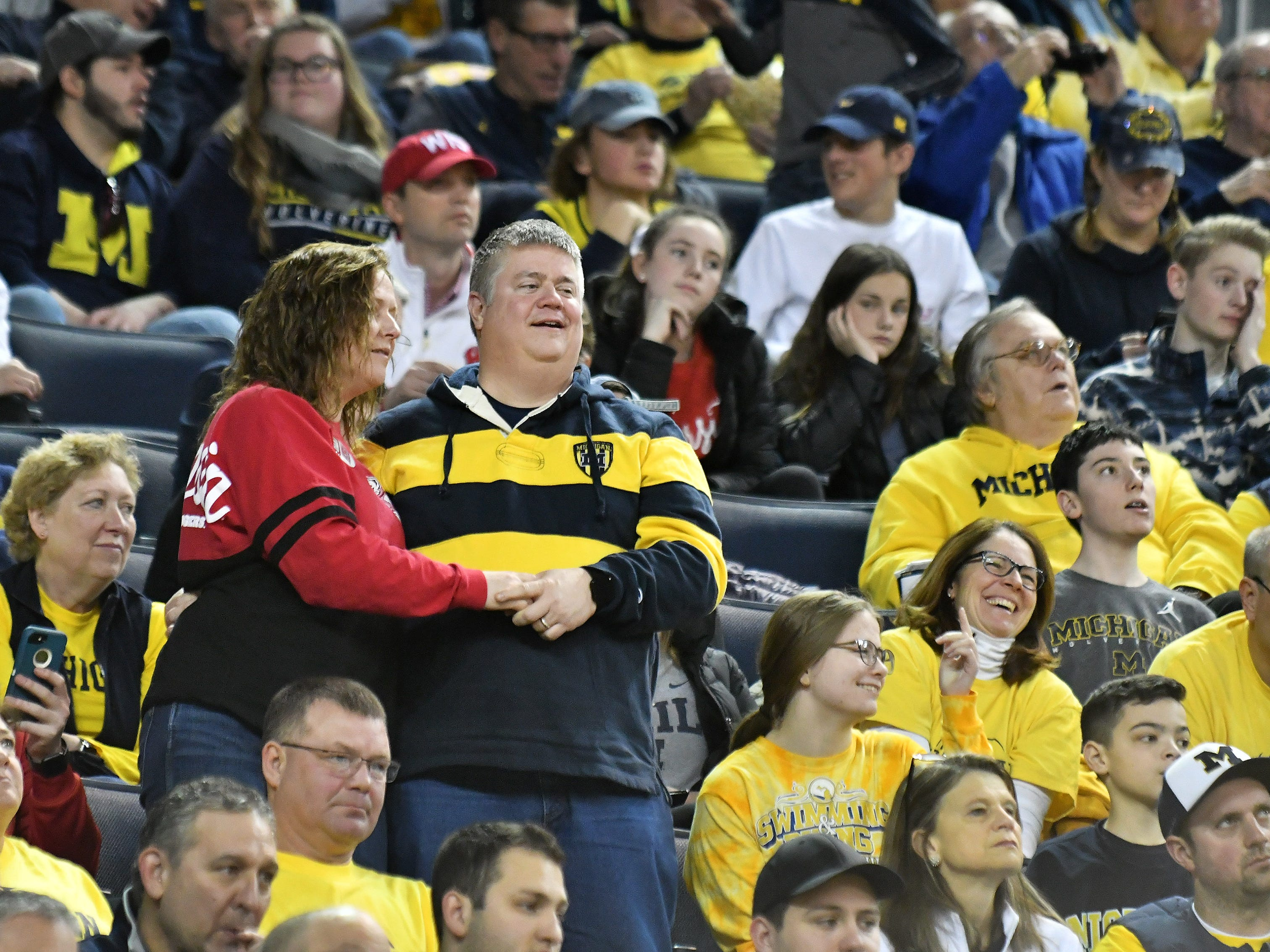 A Michigan fan and a Wisconsin fan dance together in the second half.