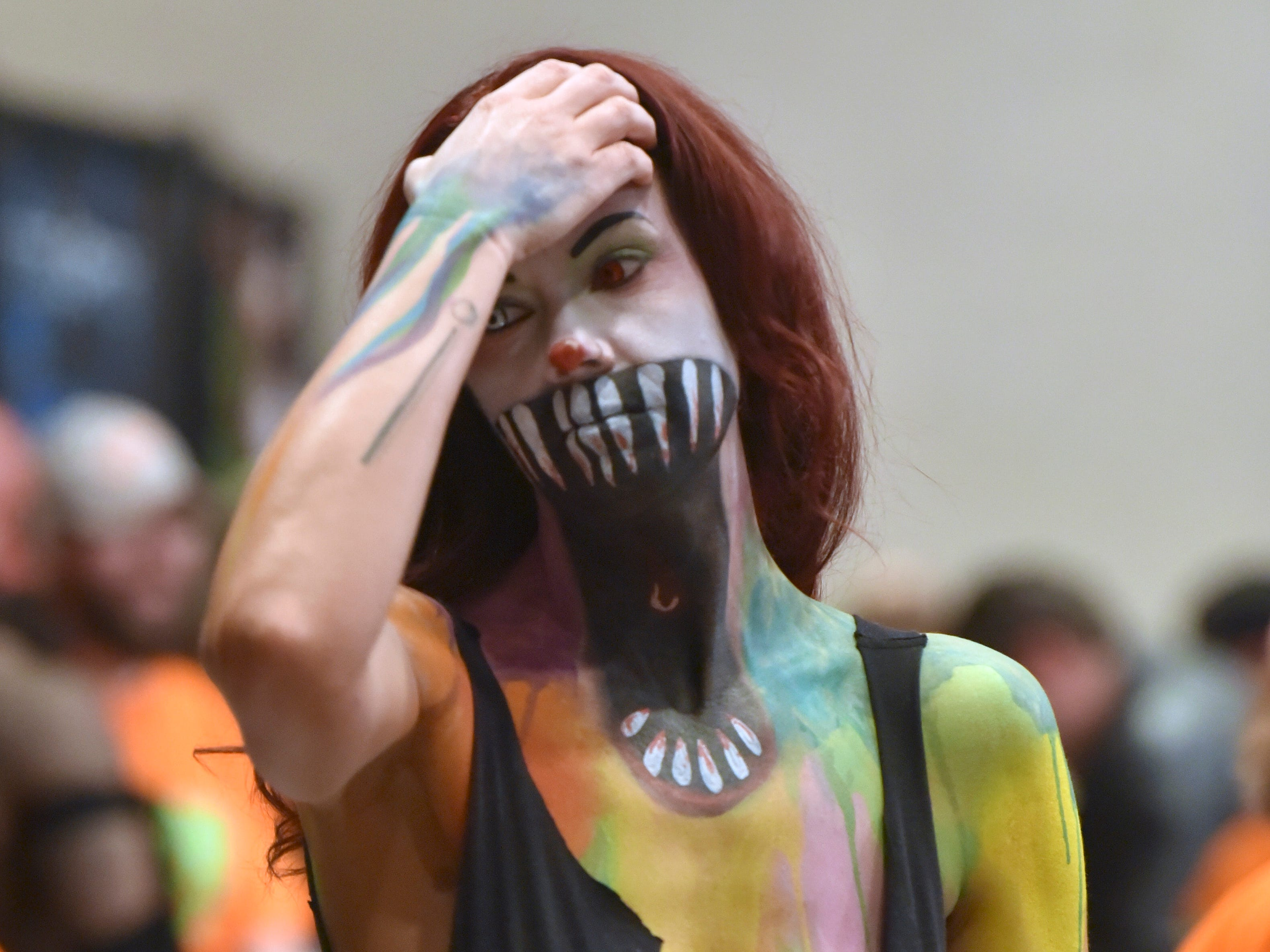 Kelly Ellison, of Dallas, TX, portrays a 'Scarey Clown,' after having her body painted by Get Dead Crew, make- up professionals.