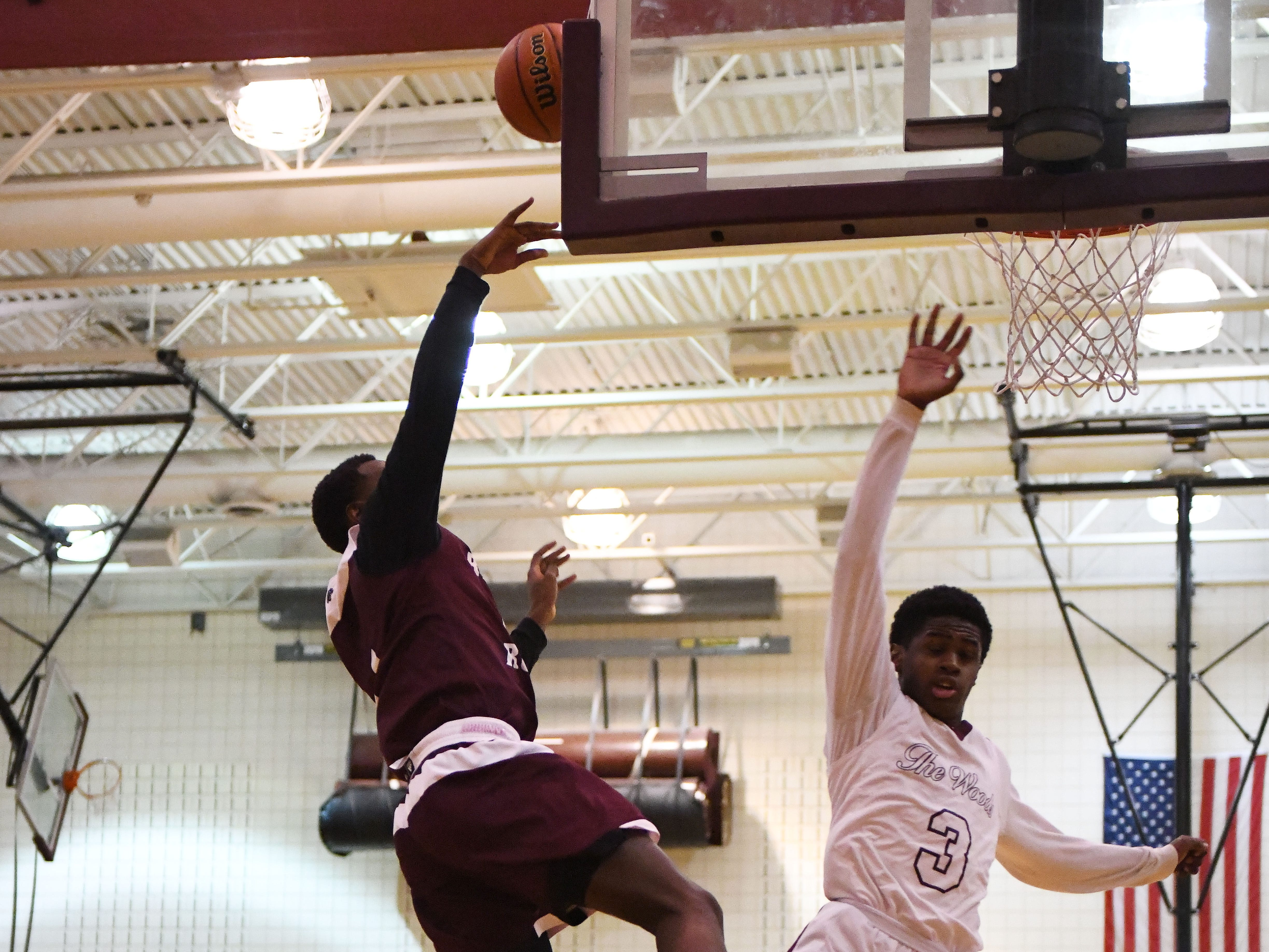 River Rouge's Donavon Freeman is fouled driving to the basket by Harper Woods' Curtis Jackson in the second half.