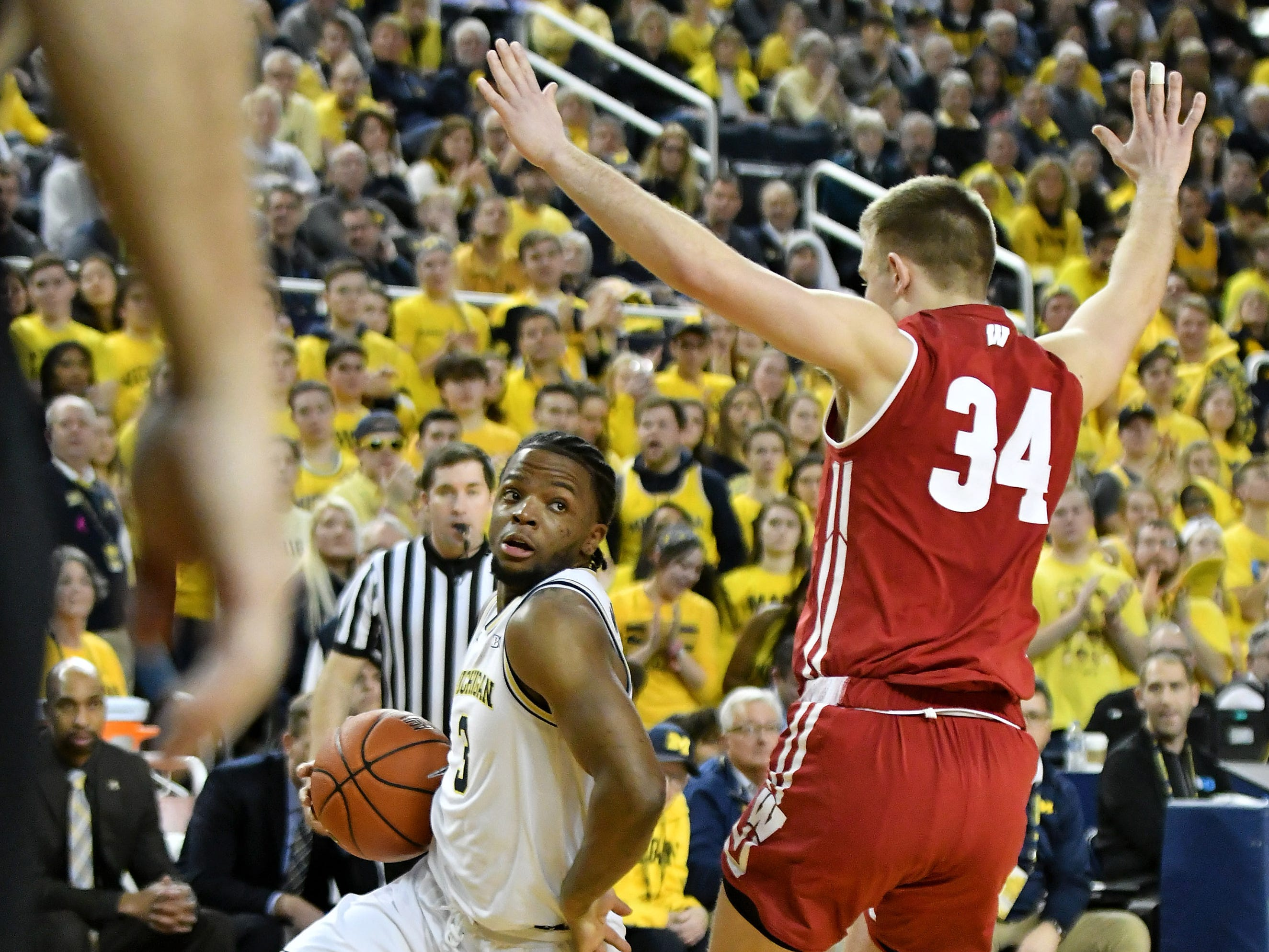 Michigan guard Zavier Simpson (3) drives around Wisconsin guard Brad Davison (34) in the second half.