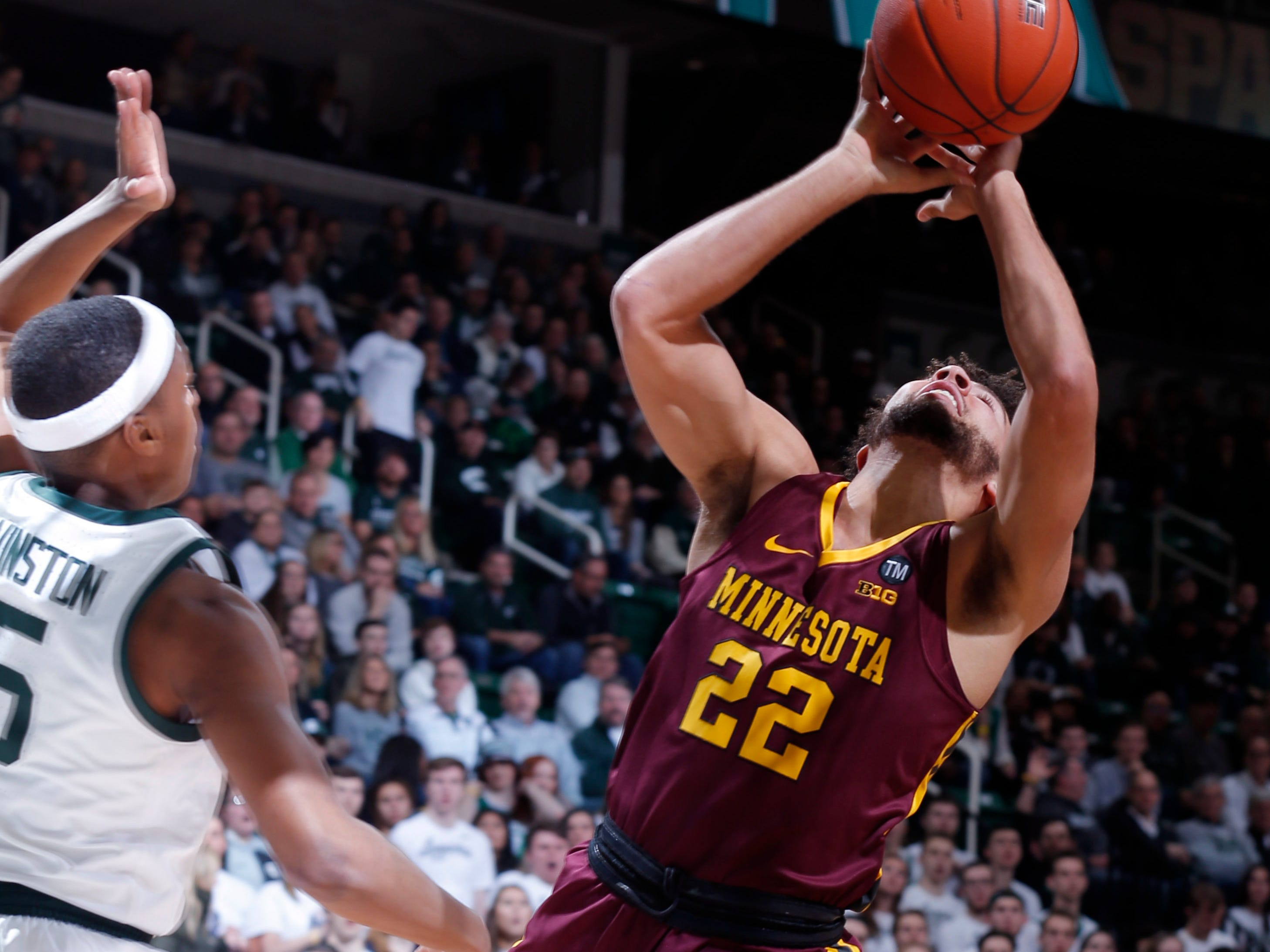 Minnesota's Gabe Kalscheur (22) puts up a shot against Michigan State's Cassius Winston during the first half.