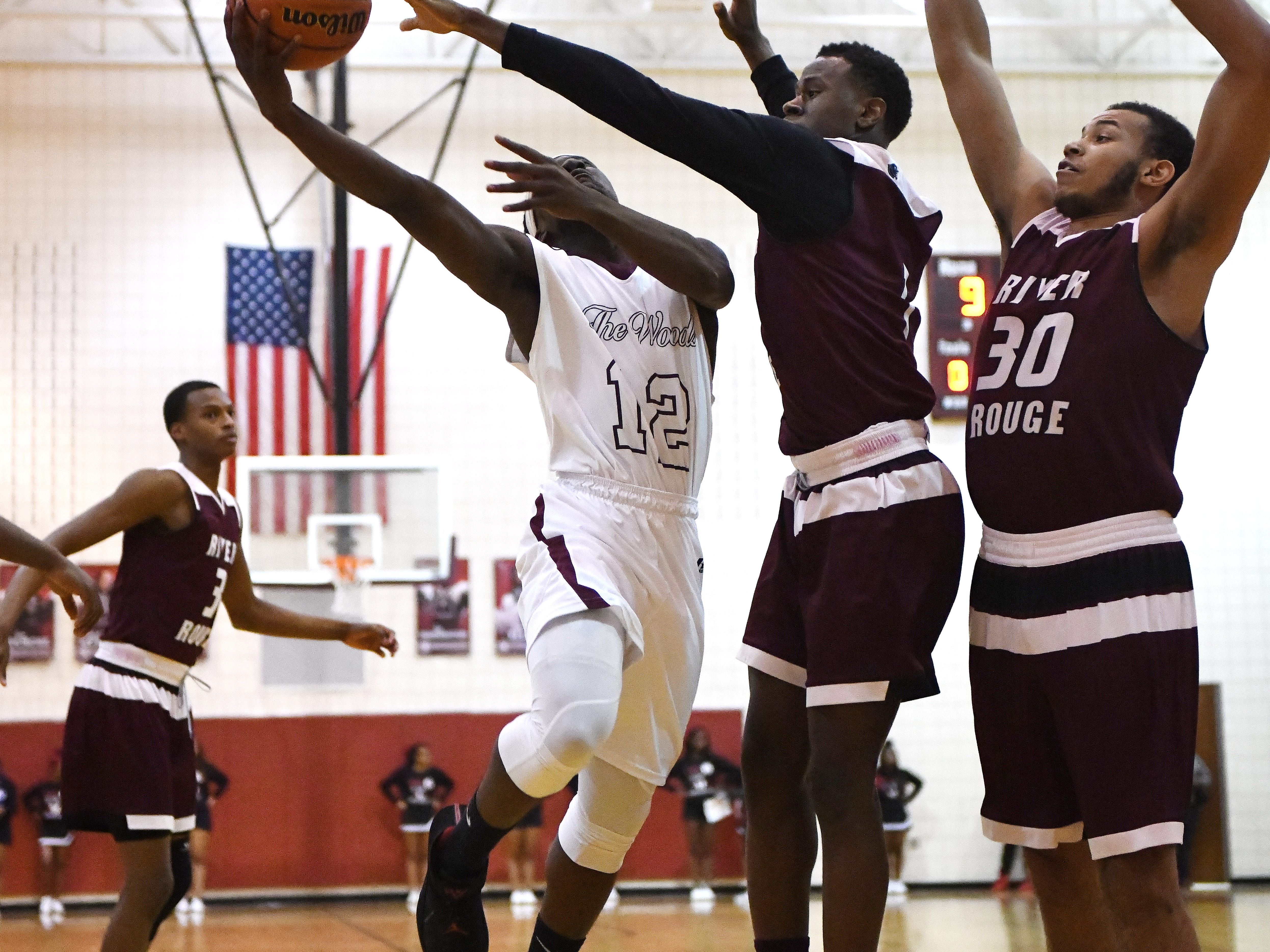 River Rouge's Donavon Freeman gets a finger on Harper Wood's Logan Garner shot but it still goes through for two in the first half.