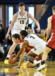 Michigan guard Zavier Simpson (3) and Wisconsin forward Ethan Happ (22) battle for the ball in the second half near Jon Teske (15).