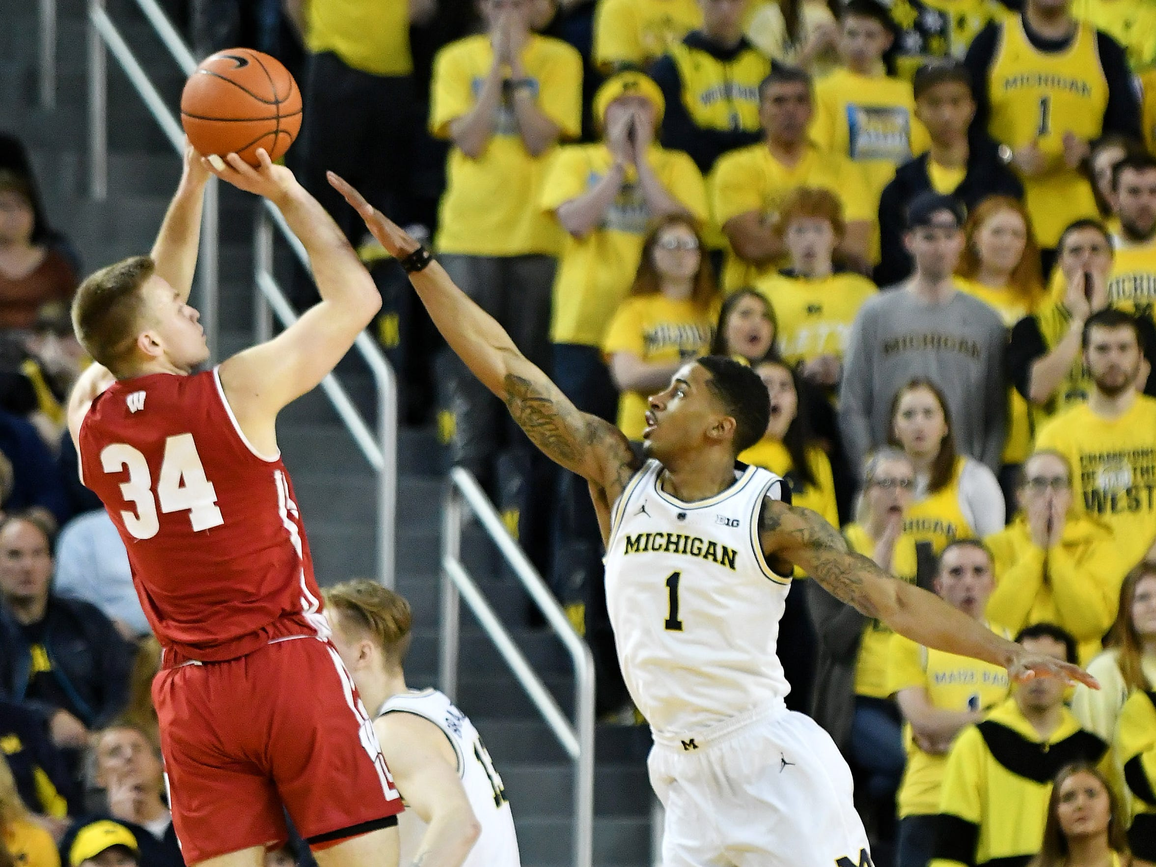 Michigan guard Charles Matthews (1) defends a shot by Wisconsin guard Brad Davison (34) in the second half.