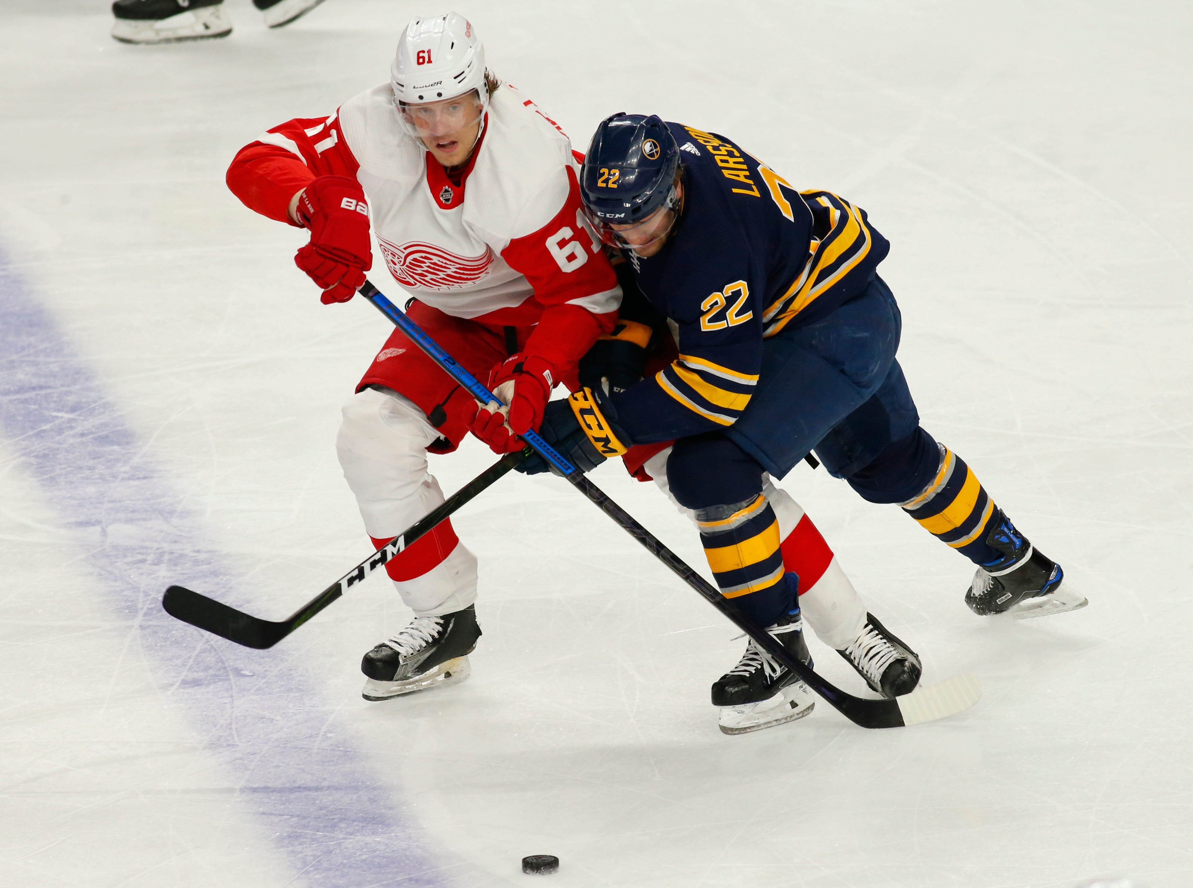 Buffalo Sabres forward Johan Larsson (22) and Detroit Red Wings forward Jacob de la Rose battle for the puck during the first period of an NHL hockey game, Saturday, Feb. 9, 2019, in Buffalo N.Y. (AP Photo/Jeffrey T. Barnes)