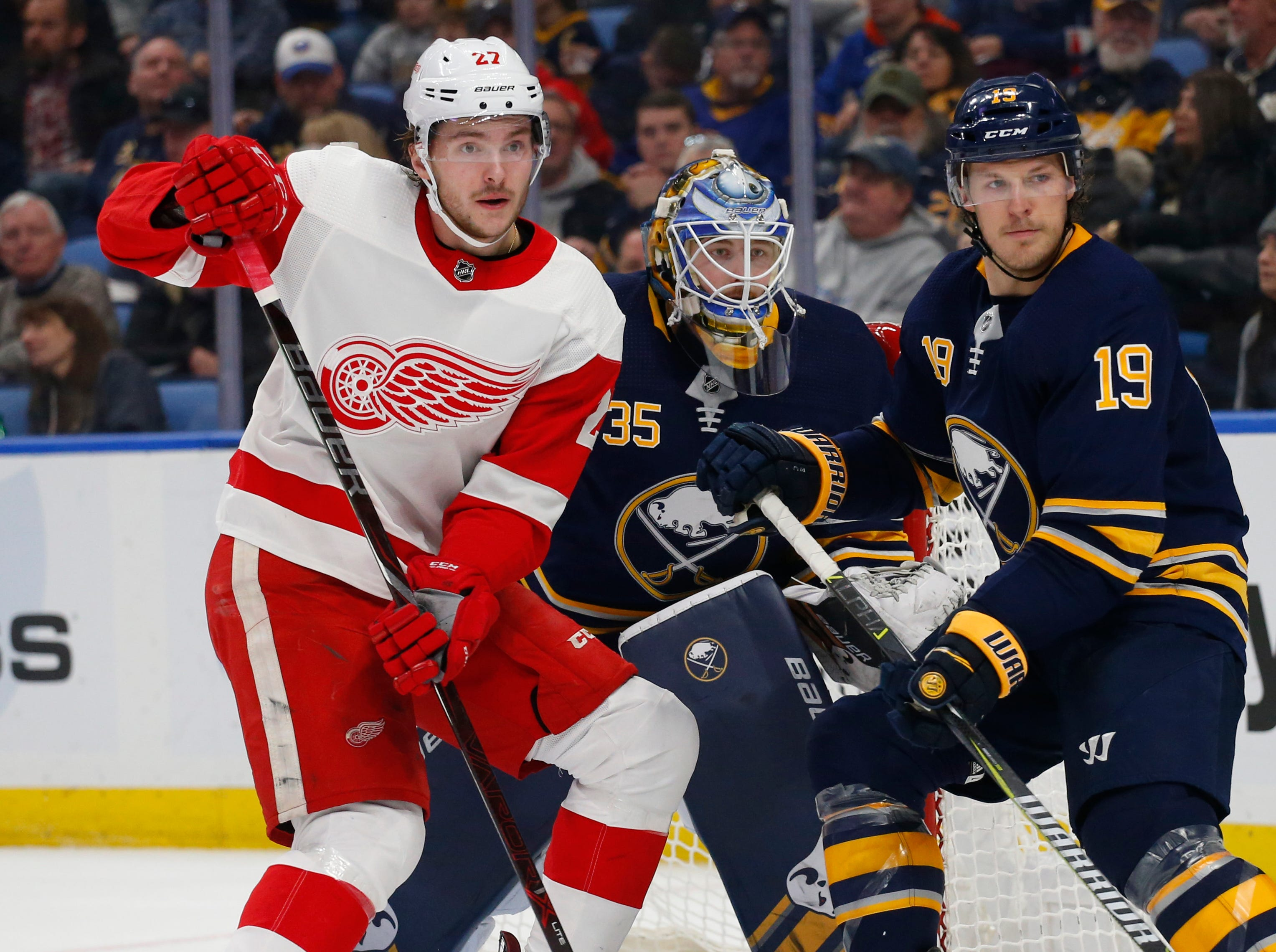 Buffalo Sabres defenseman Jake McCabe (19) and Detroit Red Wings forward Michael Rasmussen (27) battle for position in front of Buffalo Sabres goalie Linus Ullmark (35) during the second period of an NHL hockey game, Saturday, Feb. 9, 2019, in Buffalo N.Y. (AP Photo/Jeffrey T. Barnes)