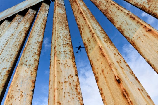 In this Dec. 23, 2018, file photo, a helicopter monitors the U.S. border fence from above, seen from Tijuana, Mexico.