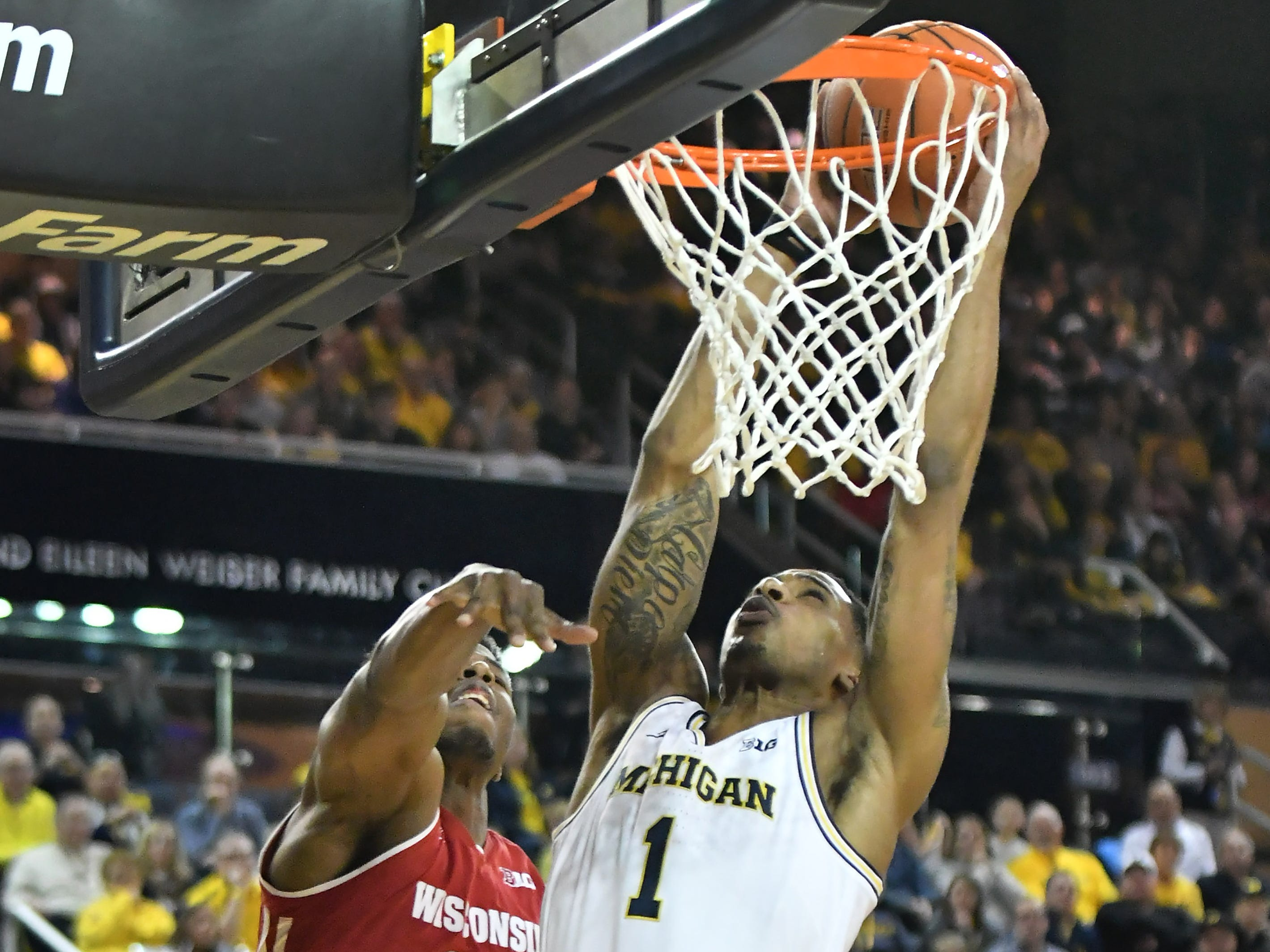 Michigan guard Charles Matthews (1) dunks over Wisconsin guard Khalil Iverson (21) in the first half.