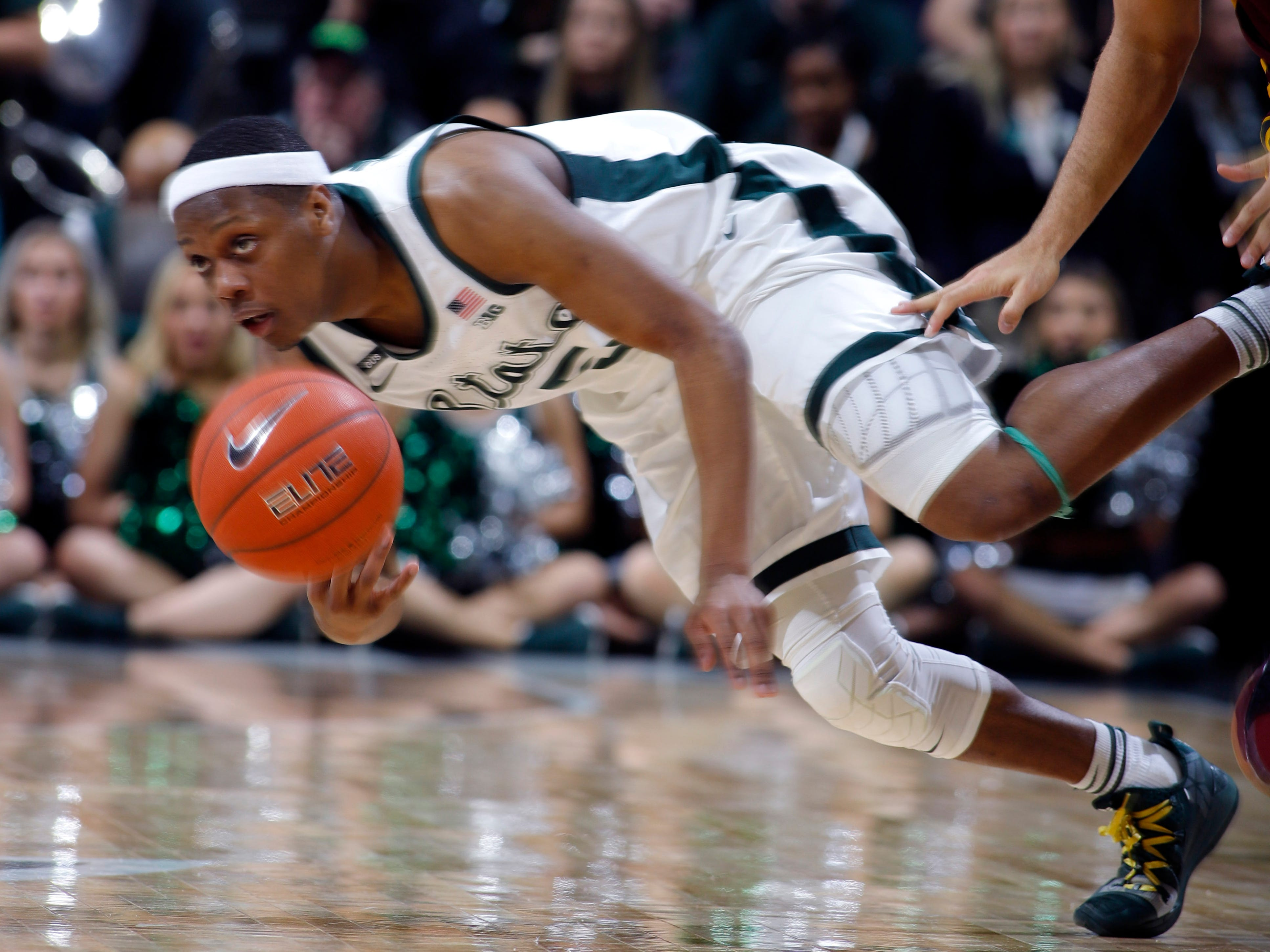 Michigan State's Cassius Winston, left, dives for the ball on a steal against Minnesota's Gabe Kalscheur, right, during the second half.