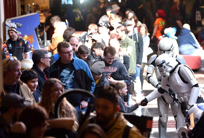 Great Lakes Garrison of the 501st Legion members Stormtrooper TK6778, portrayed by Derek Lane-Waters, right, of Rochester Hills, shakes hands with Calvin Thompson, 7, of Hamburg Twp., as he waits in line with family members to buy tickets to Astronomicon 2. Lane-Waters, originally from England, is joined by Clone Trooper CT7859, portrayed by Joe Fera, right-rear, of Marine City, at the pop-culture convention, at the Wyndham Garden Sterling Heights, Saturday, February 9, 2019. The event continues from 11am to 5pm, Sunday. For more information visit https://www.astronomicon.com (Todd McInturf, The Detroit News)2019.