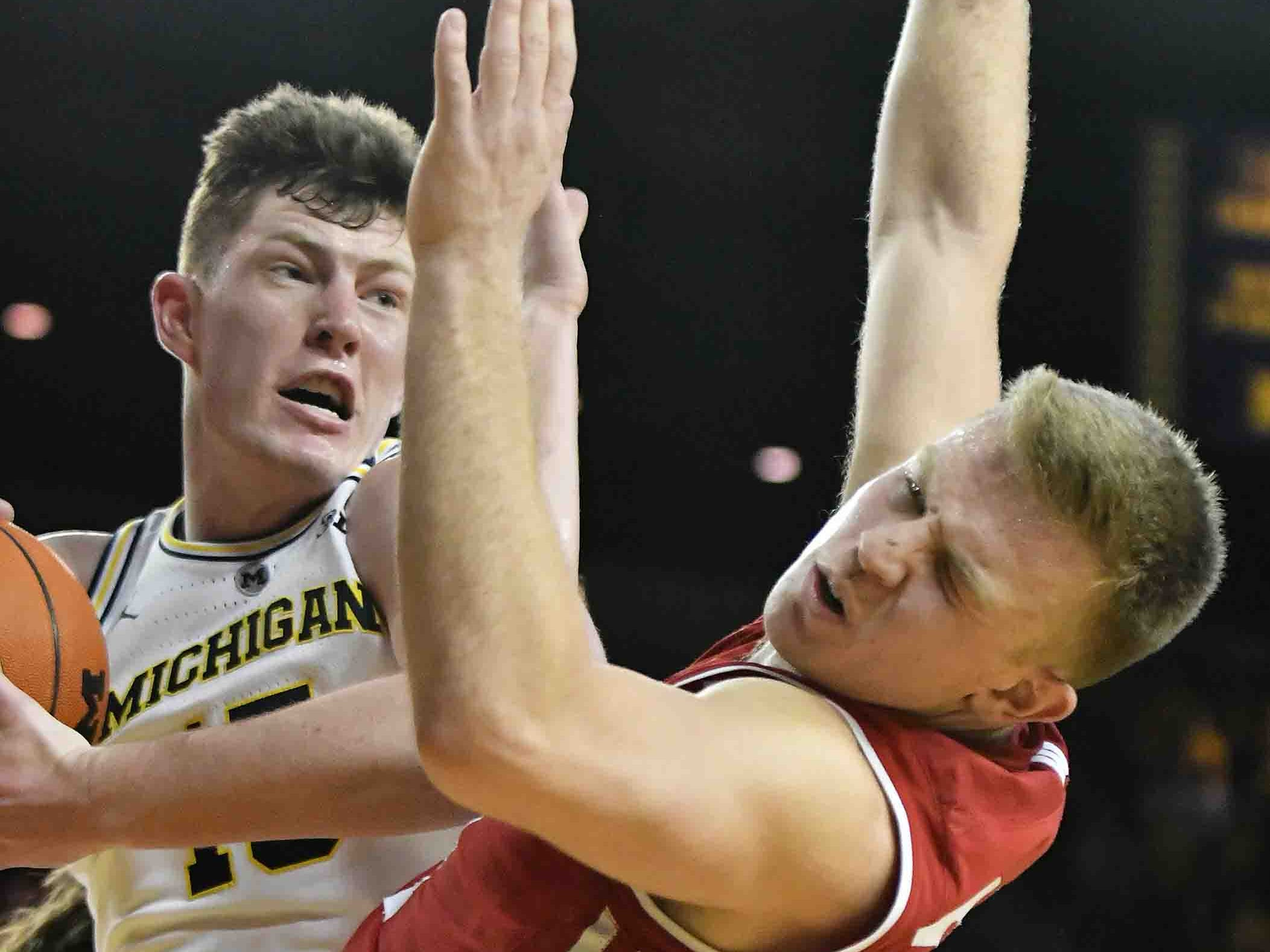 Michigan center Jon Teske (15) comes up with a rebound near Wisconsin guard Brad Davison (34) the second half.