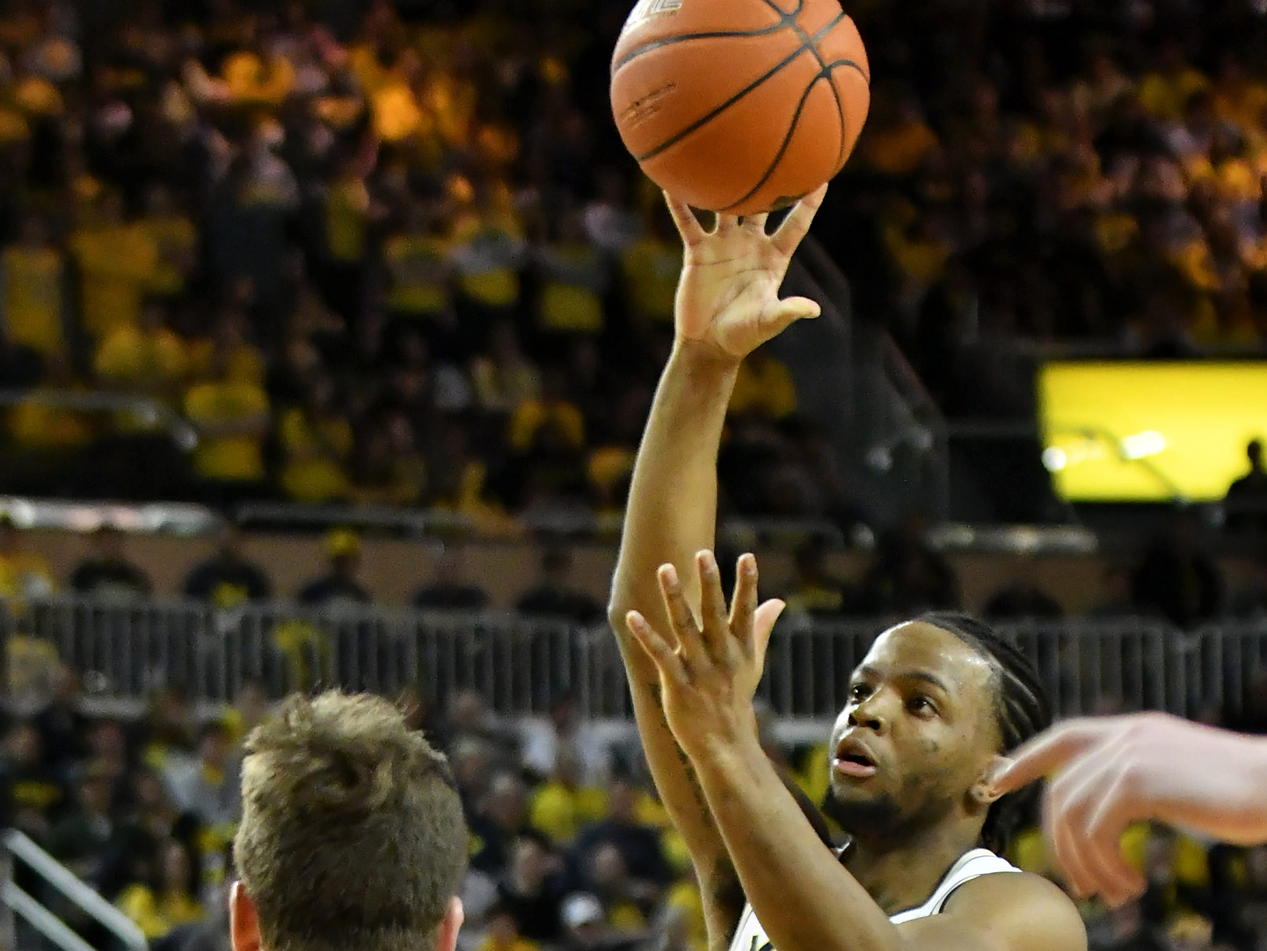 Michigan guard Zavier Simpson (3) gives an alley oop to Jon Teske, out of the frame, in the second half.