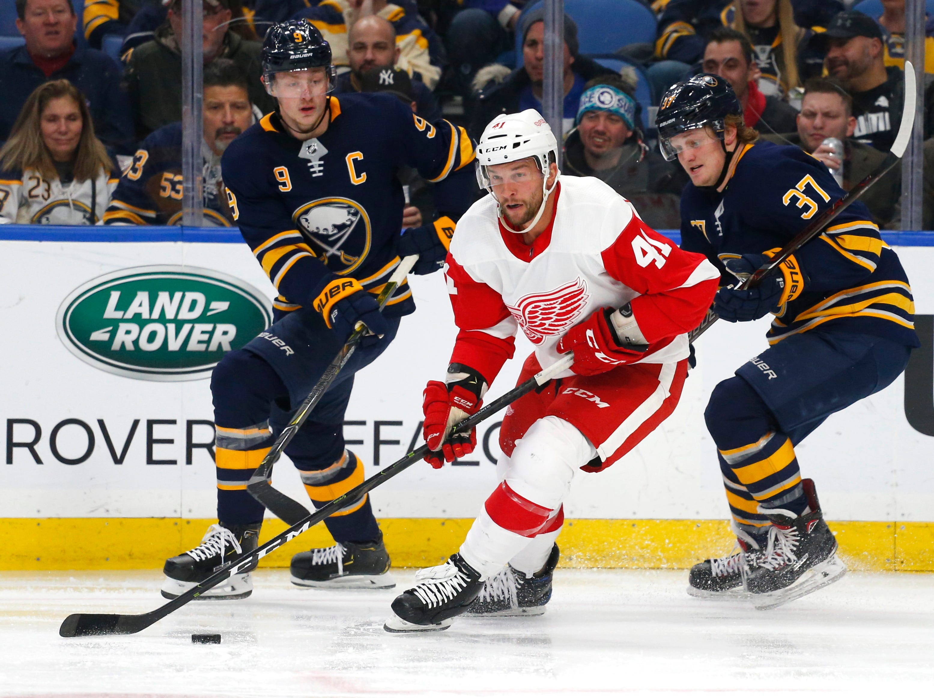 Detroit Red Wings forward Luke Glendening (41) carries the puck past Buffalo Sabres forwards Jack Eichel (9) and Casey Mittelstadt (37) during the second period of an NHL hockey game, Saturday, Feb. 9, 2019, in Buffalo N.Y. (AP Photo/Jeffrey T. Barnes)