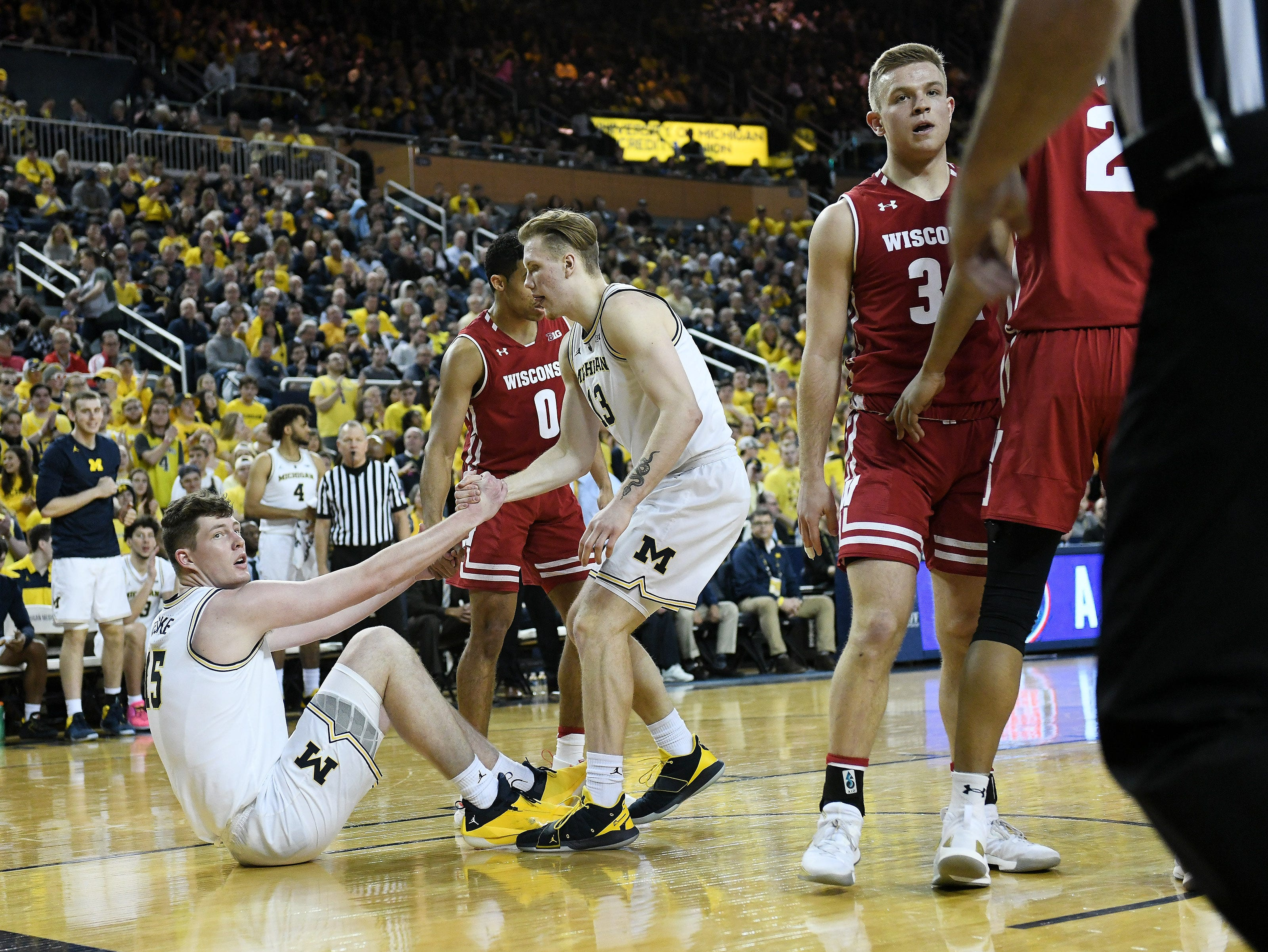 Michigan forward Ignas Brazdeikis (13) helps up his teammate Jon Teske in the second half.