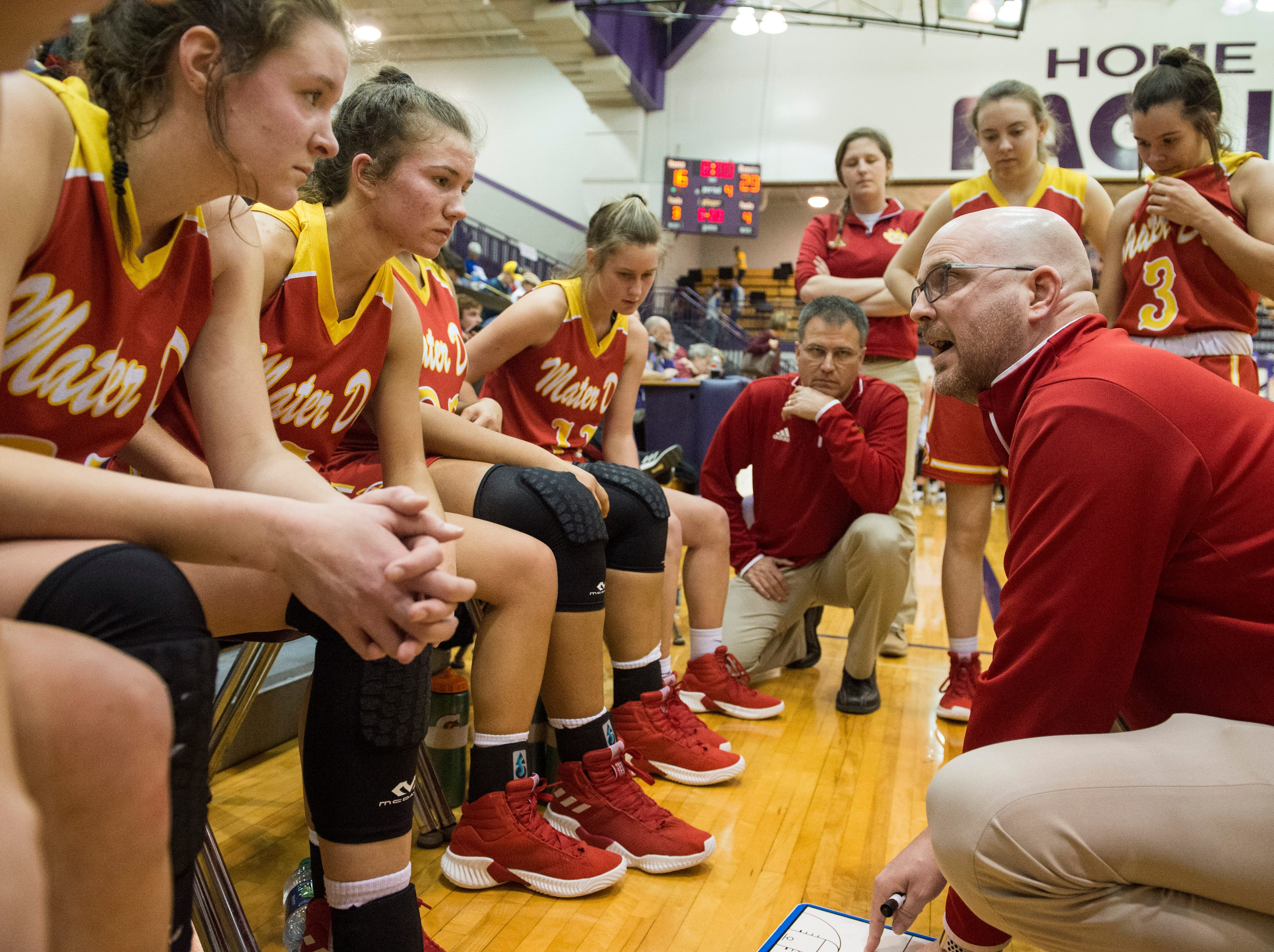Mater Dei Head Coach Chad Breeden directs players during a timeout in the IHSAA Class 2A Girls' Basketball Regional #12 game against the South Ripley Raiders at Paoli Jr. Sr. high school Saturday, Feb. 9, 2019. Mater Dei Won, 39-23.