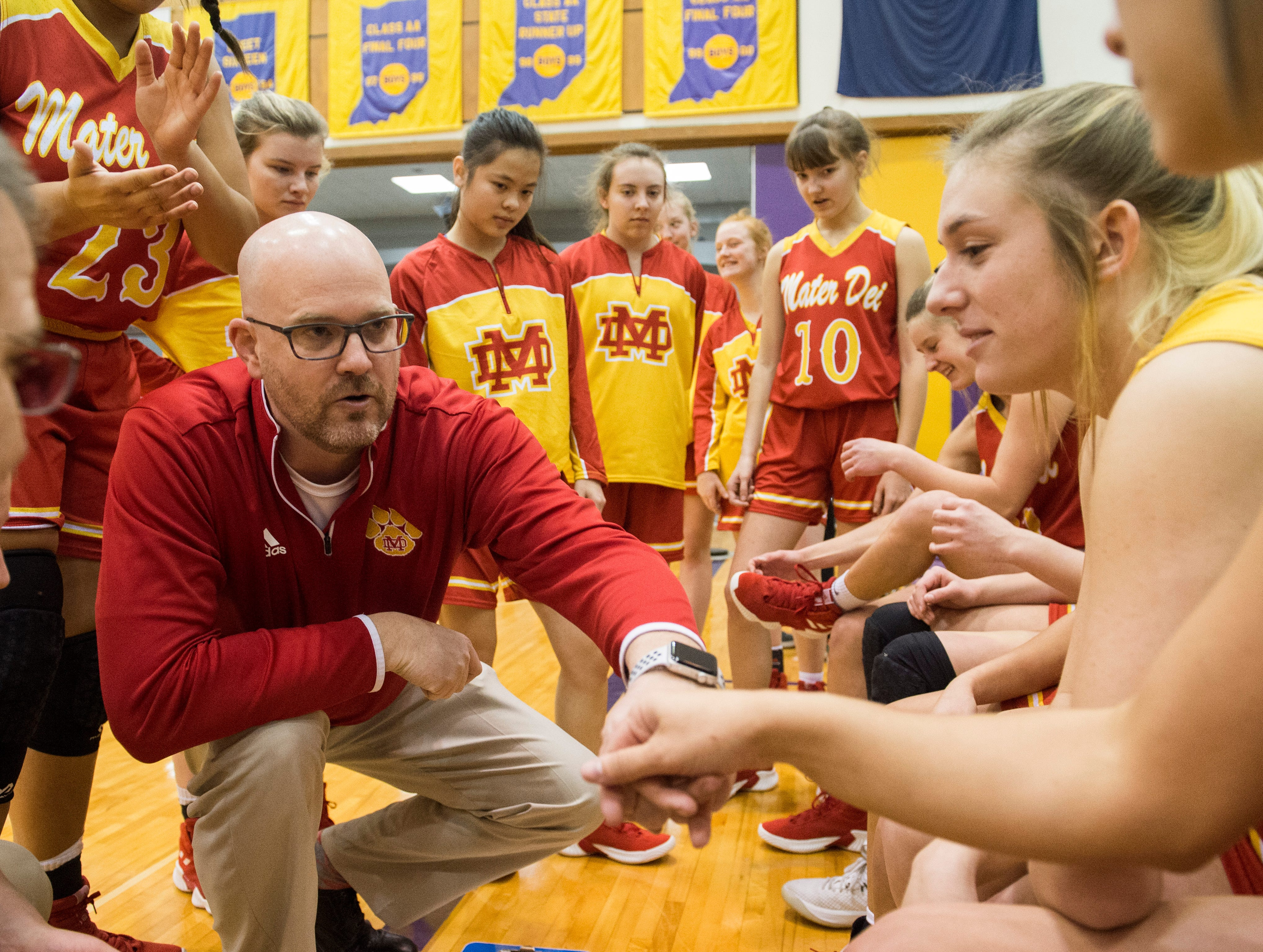 Mater Dei Head Coach Chad Breeden fist bumps the starters before the IHSAA Class 2A Girls' Basketball Regional #12 game against the South Ripley Raiders at Paoli Jr. Sr. high school Saturday, Feb. 9, 2019. Mater Dei Won, 39-23.