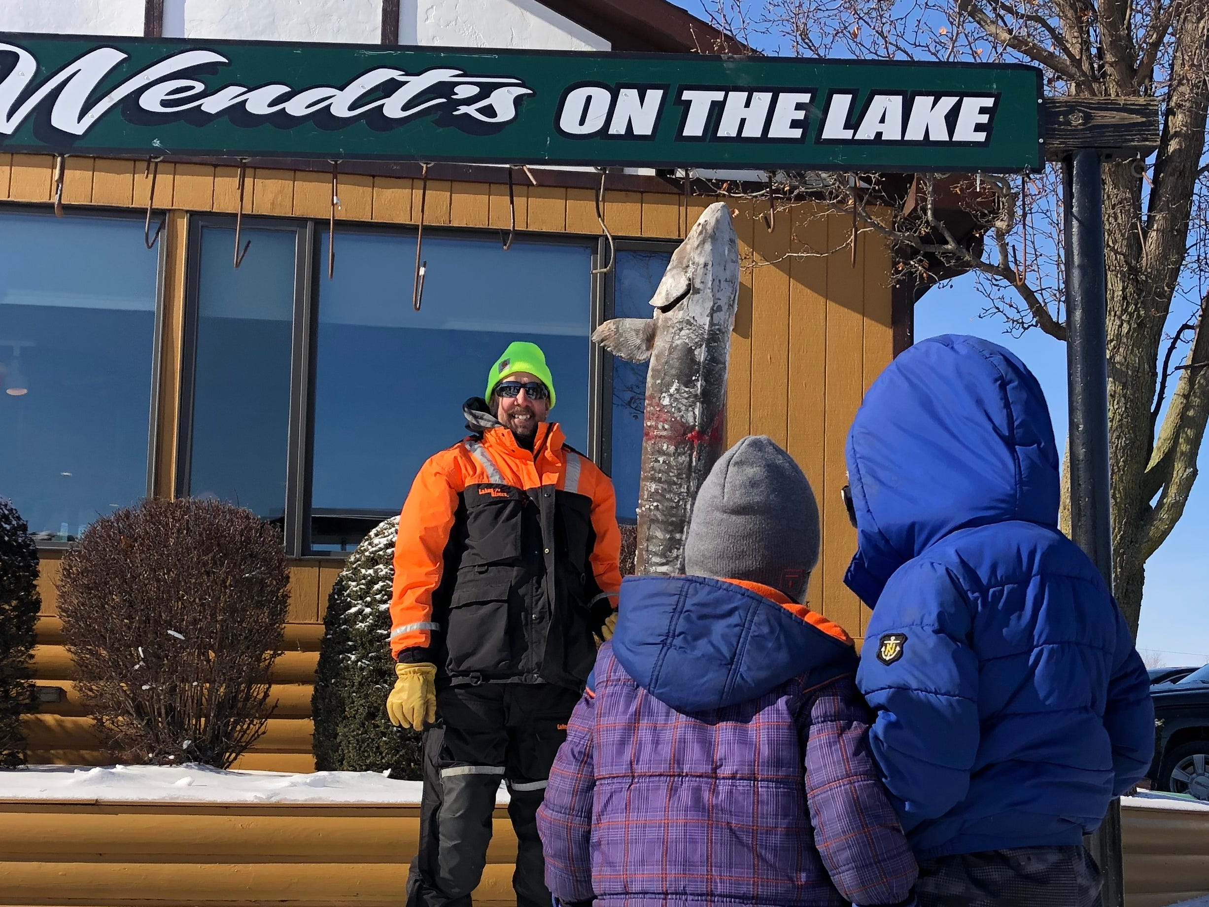 Jack and James Minha, ages 6 and 4, of Oshkosh look at Fond du Lac resident Doug King's 70-pound sturgeon outside Wendt's on the Lake. King speared his fish Feb. 9, 2019, on Lake Poygan.