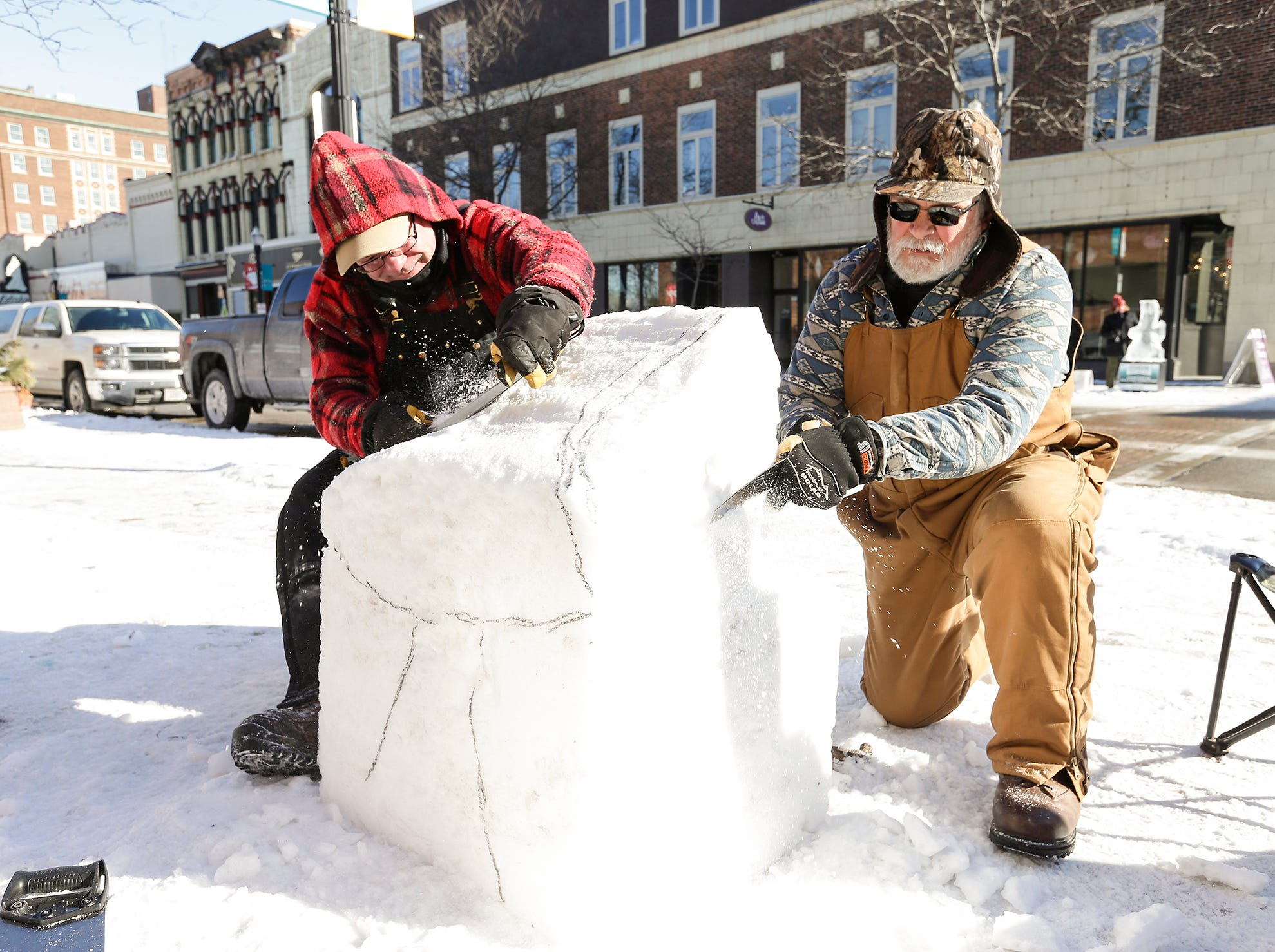 Randy Jahn of Lomira and David King of Randolph work on a snow sculpure Friday, February 8, 2019 on Main Street in downtown Fond du Lac during Sturgeon Spectacular. Sturgeon Spectacular is a weeklong celebration of the lake sturgeon spearing season and includes events on and off the ice in the Fond du Lac area. Doug Raflik/USA TODAY NETWORK-Wisconsin