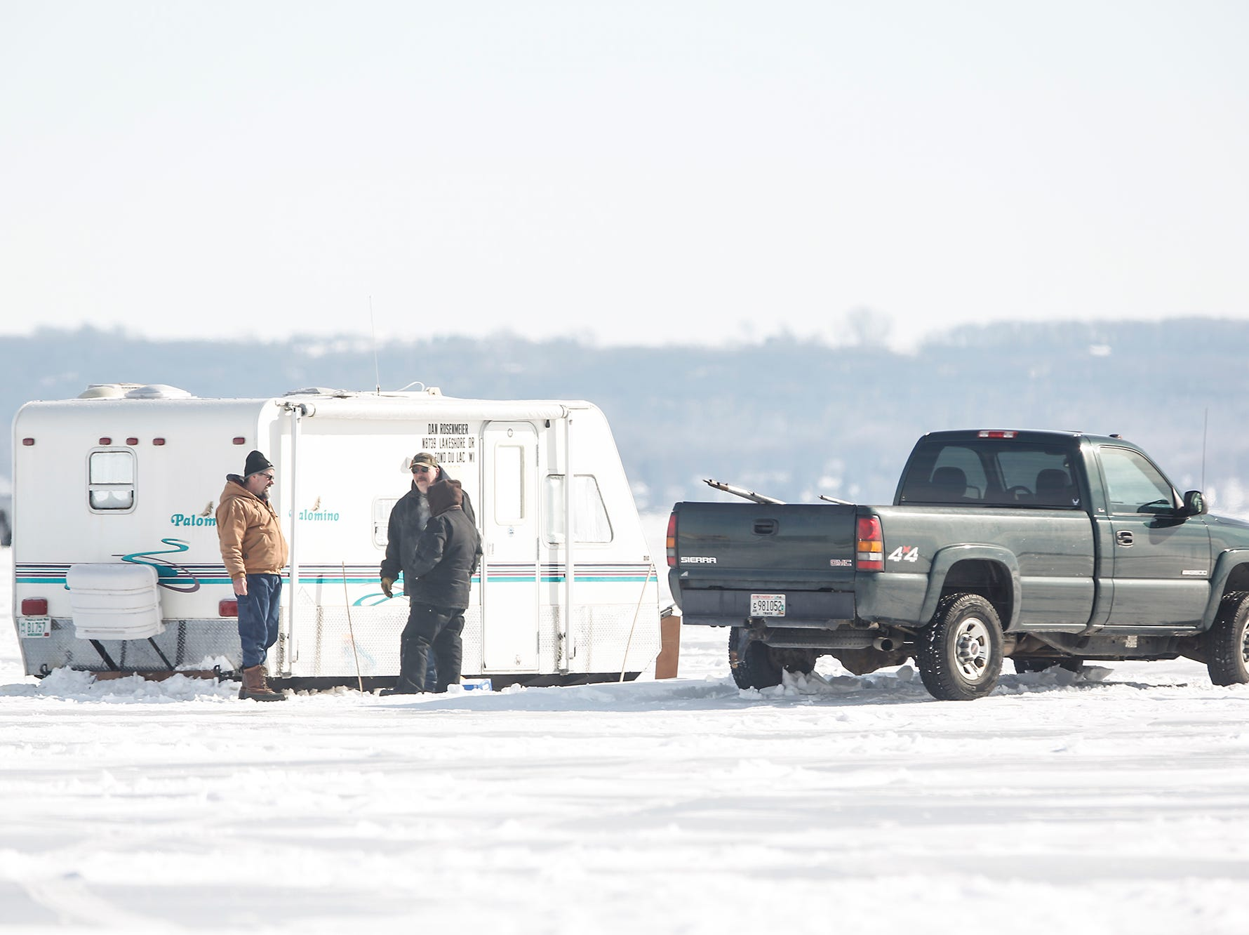Three people stand outside a fish shanty Saturday, February 9, 2019 on Lake Winnebago between Fond du Lac and Oshkosh. Sturgeon spearing season runs from February 9, 2019 through February 24, 2019 on Lake Winnebago or until any