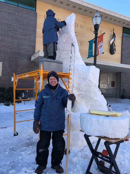 Mike Lechtenberg of the Milwaukee area-based Scupltora Borealis snow sculpting team poses with a saw used to cut holes in the ice as his son Bill Lechtenberg begins to carve the wings of an eagle into their creation. The duo, along with Josh Jakubowski of Port Washington, were competing for a state snow scuplting title Saturday in downtown Fond du Lac.