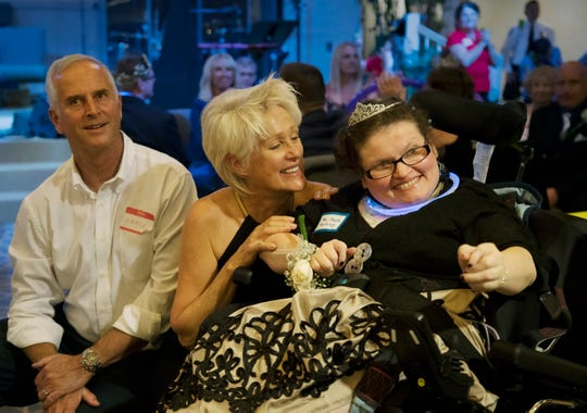 "Judy Peterson, center, celebrates with Sheila Keithley, right, during the ""Night to Shine"" event recently at Sanibel Community Church on Sanibel Island. The annual event celebrates people with special needs and is presented by the Tim Tebow Foundation. More than 600 churches across the country participated."