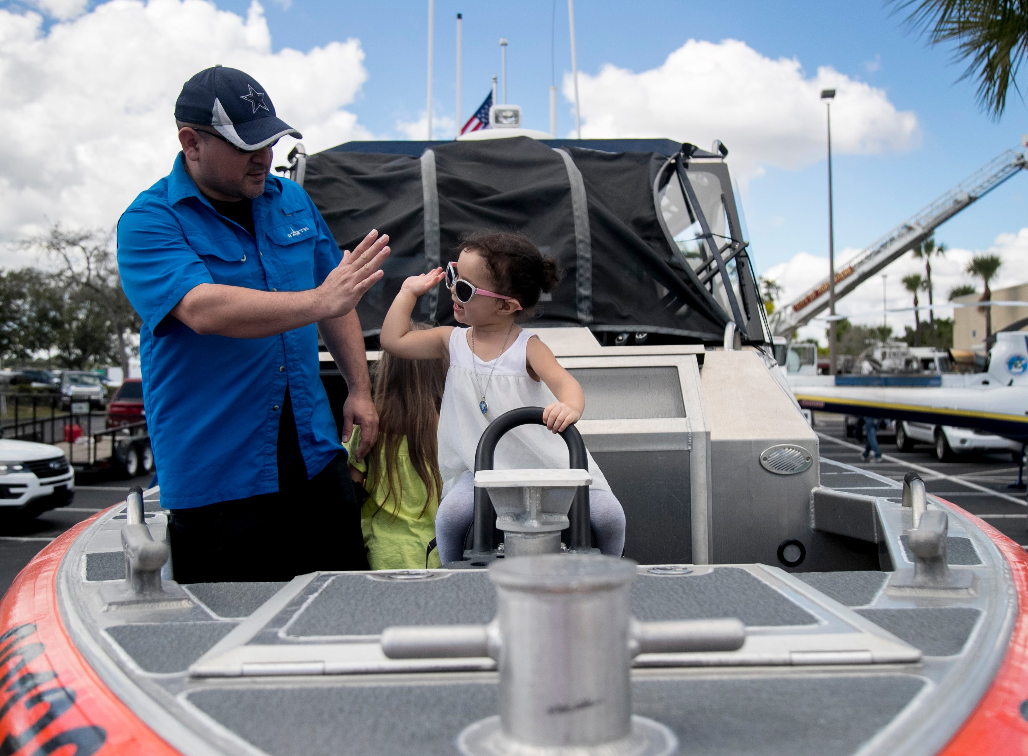 Isabella Dussan, 2, gives her dad Andre a high five aboard the Coast Guard boat on display at the STEMtastic Day of Discovery on Saturday, Feb. 9, 2019, in Fort Myers.
