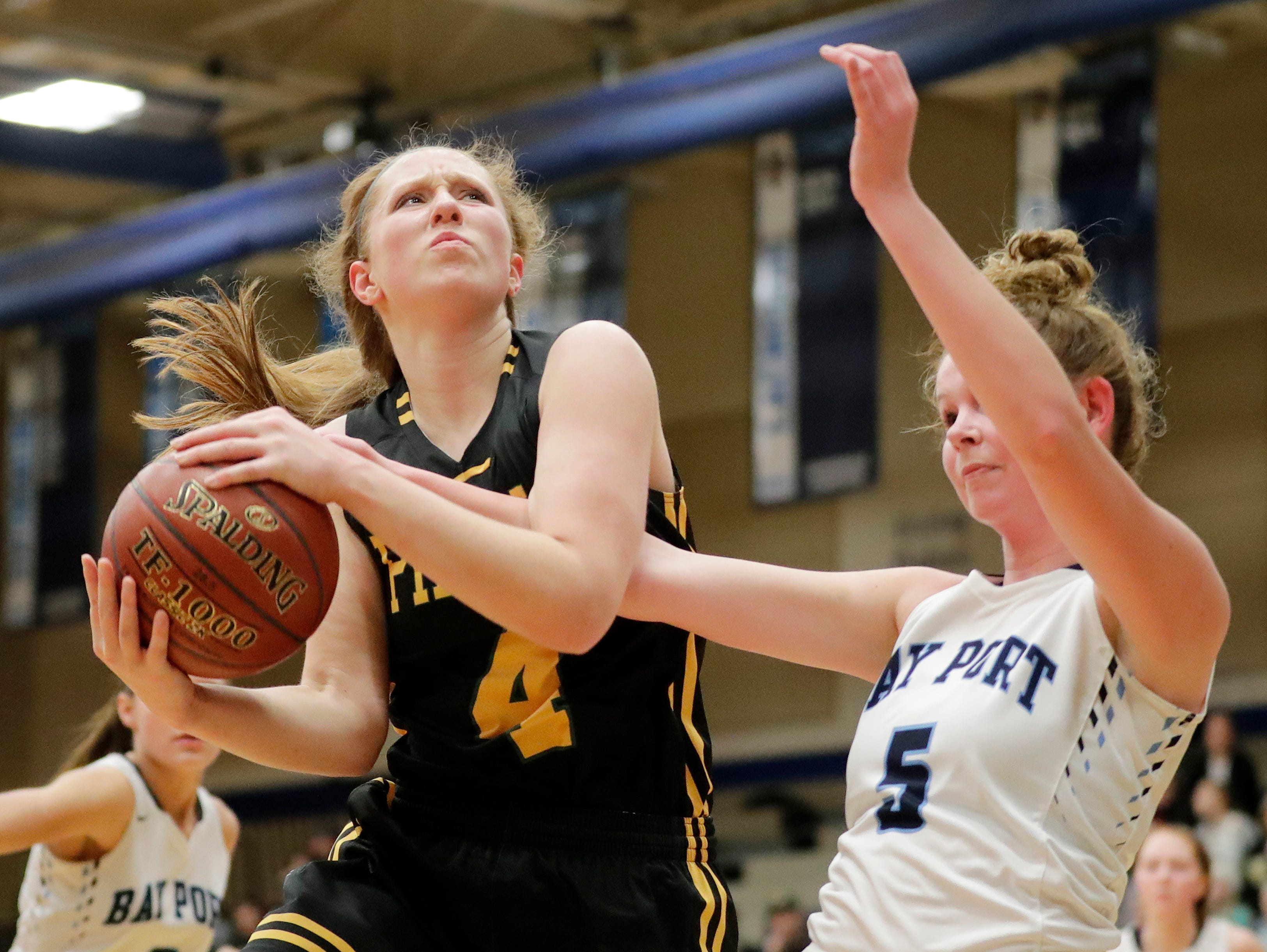 Green Bay Preble's Kendall Renard (4) grabs a rebound against Bay Port's Peyton Coughlin (5) in a FRCC girls basketball game at Bay Port high school on Friday, February 8, 2019 in Suamico, Wis.