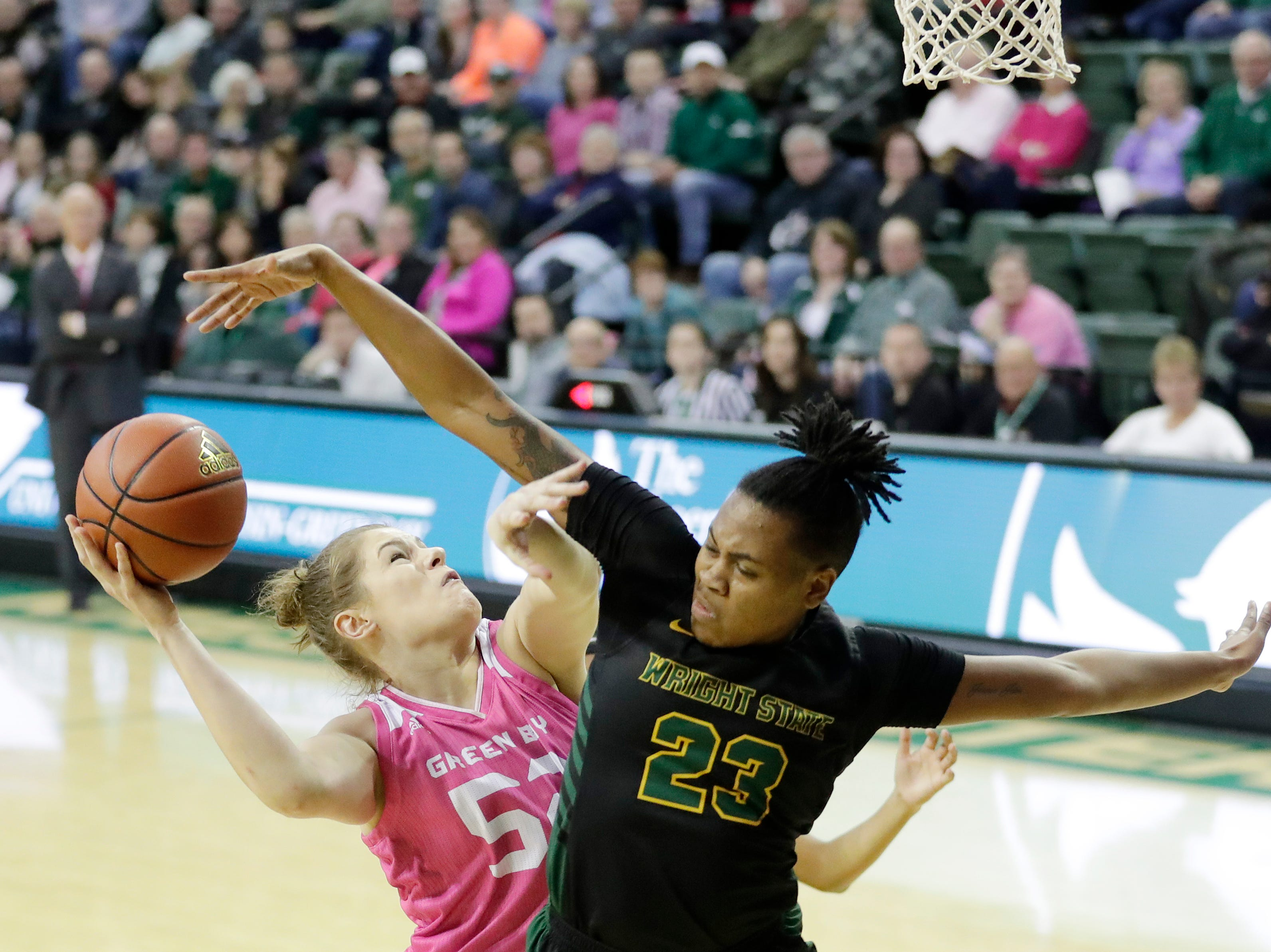 Green Bay Phoenix forward/center Madison Wolf (52) draws a foul by Wright State Raiders guard Symone Simmons (23) in a Horizon League women's basketball game at the Kress Center on Saturday, February 9, 2019 in Green Bay, Wis.