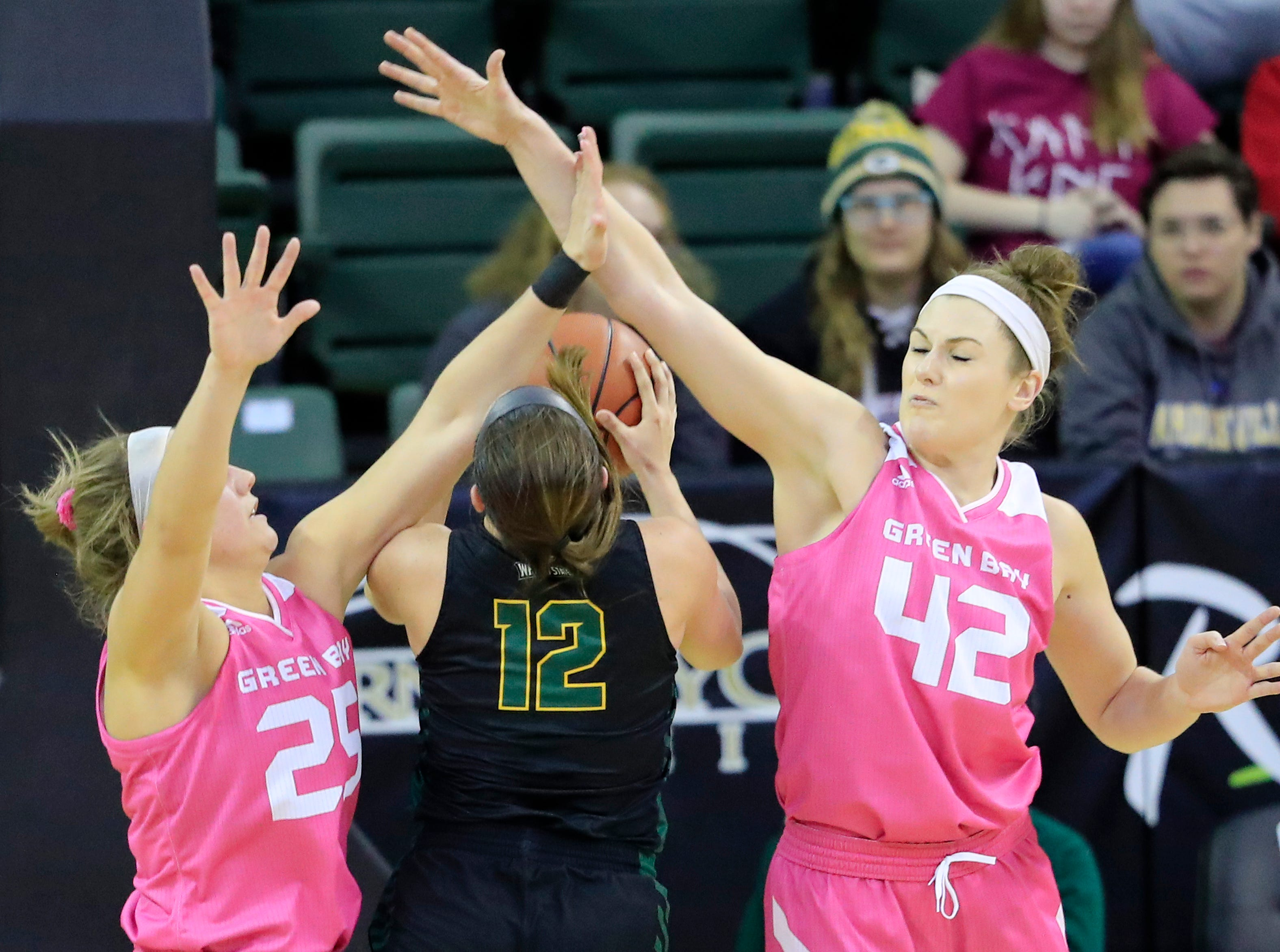 Green Bay Phoenix guard/forward Lyndsey Robson (25) and forward/center Mackenzie Wolf (42) defend a shot by Wright State Raiders guard Mackenzie Taylor (12) in a Horizon League women's basketball game at the Kress Center on Saturday, February 9, 2019 in Green Bay, Wis.