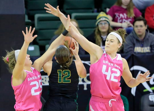 Green Bay Phoenix guard-forward Lyndsey Robson (25) and forward-center Mackenzie Wolf (42) defend a shot by Wright State Raiders guard Mackenzie Taylor (12).