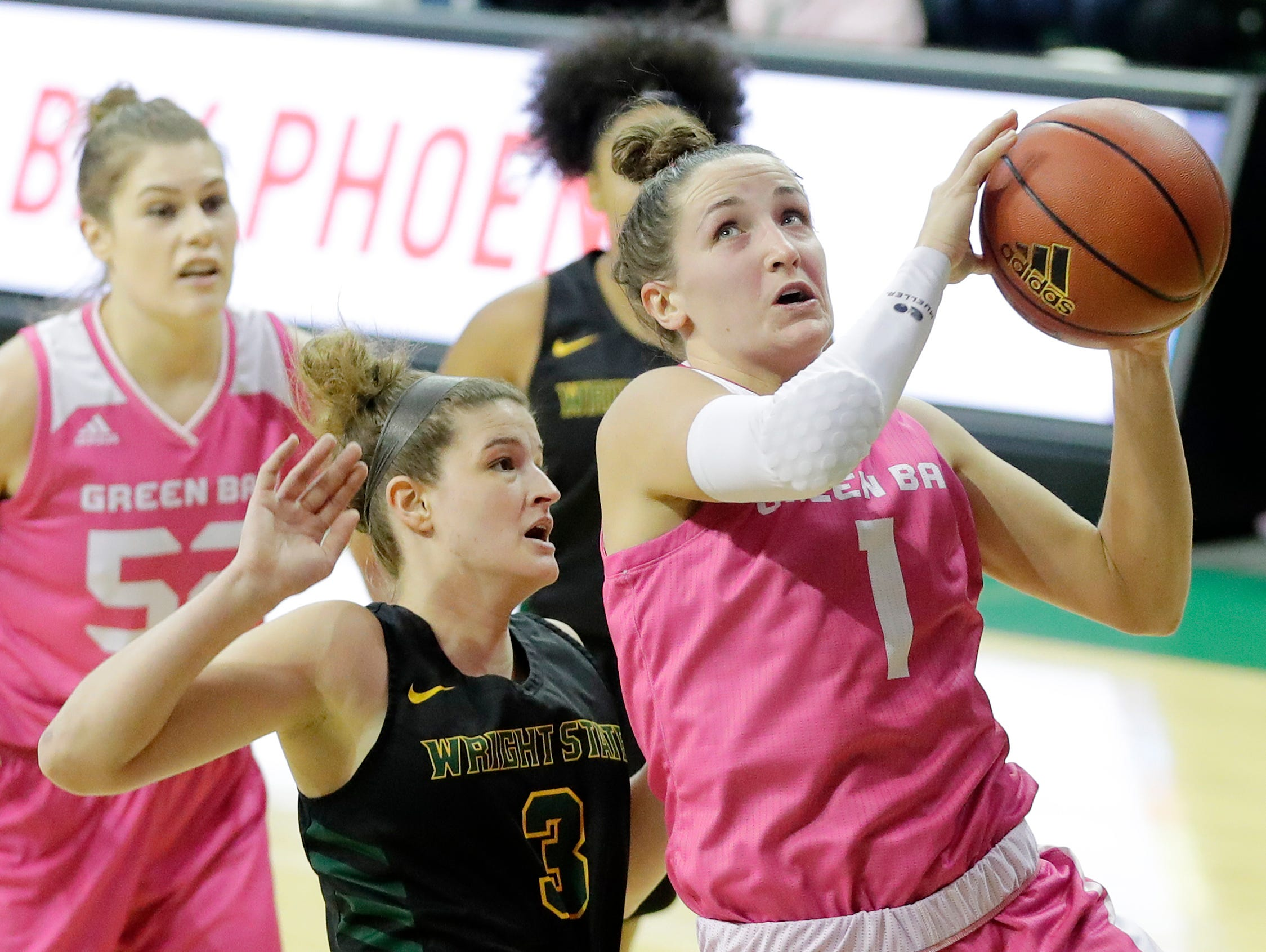 Green Bay Phoenix guard Jen Wellnitz (1) drives to the basket against Wright State Raiders guard Emily Vogelpohl (3) in a Horizon League women's basketball game at the Kress Center on Saturday, February 9, 2019 in Green Bay, Wis.
