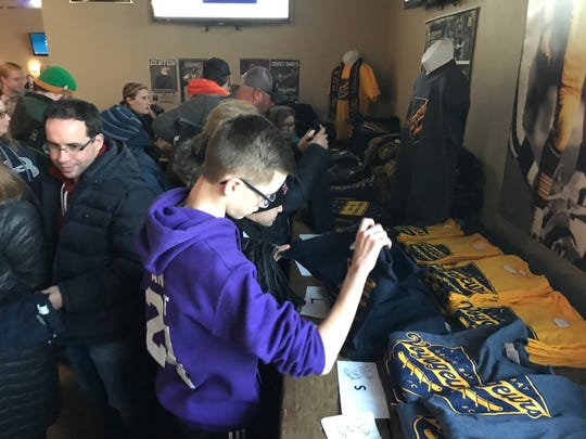 Green Bay area soccer fans look at T-shirts and scarves for sale bearing the crest and colors of Green Bay Voyageurs FC during an unveiling at Green Bay Distillery.