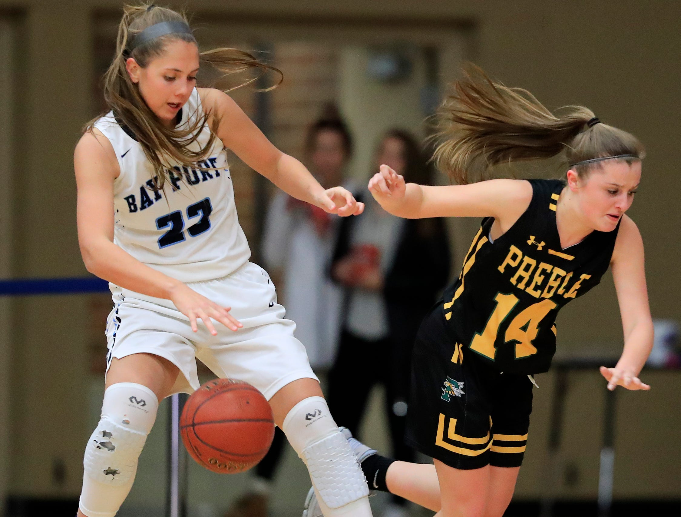 Bay Port's Emma Nagel (23) collides with Green Bay Preble's Taylor Sleger (14) in an FRCC girls basketball game at Bay Port high school on Friday, February 8, 2019 in Suamico, Wis.