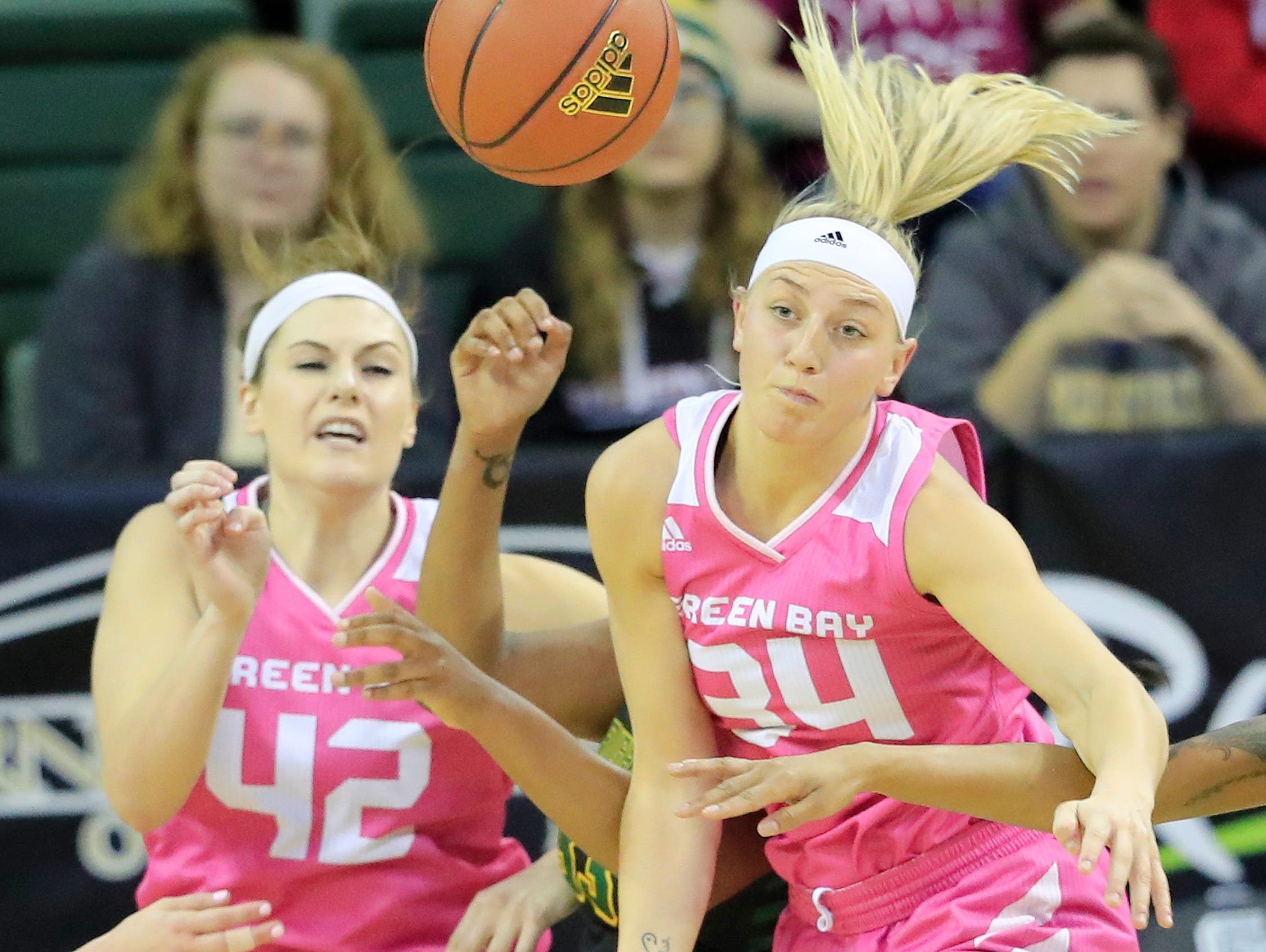 Green Bay Phoenix forward/center Mackenzie Wolf (42) and forward Carly Mohns (34) compete for a rebound against the Wright State Raiders in a Horizon League women's basketball game at the Kress Center on Saturday, February 9, 2019 in Green Bay, Wis.