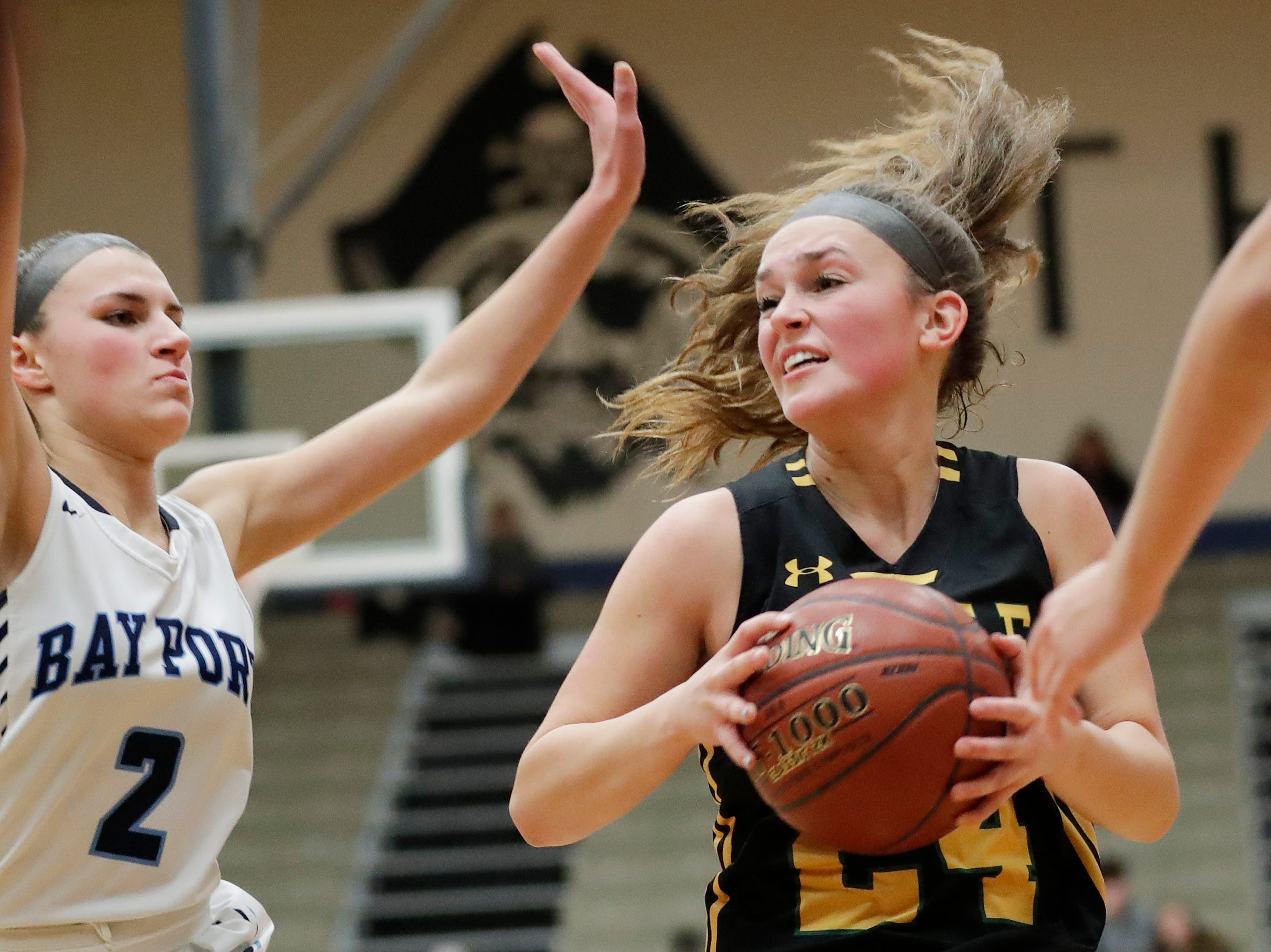 Green Bay Preble's Ella Bialkowski (24) dribbles past Bay Port's Grace Krause (2) in a FRCC girls basketball game at Bay Port high school on Friday, February 8, 2019 in Suamico, Wis.