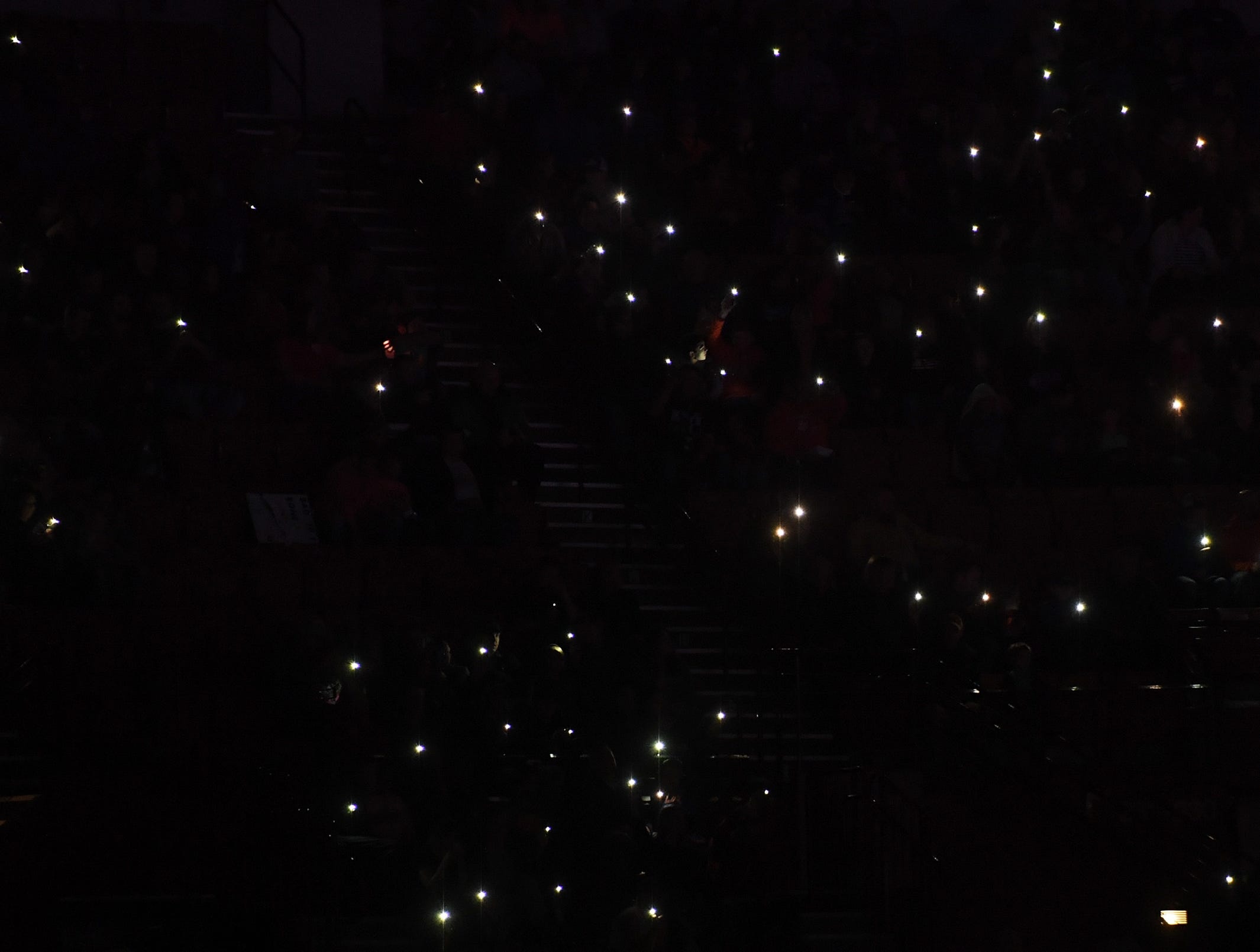 Audience members light up their phones to honor service members and emergency personnel at the start of Monster Jam at Bon Secours Wellness Arena Friday, Feb. 8, 2019.